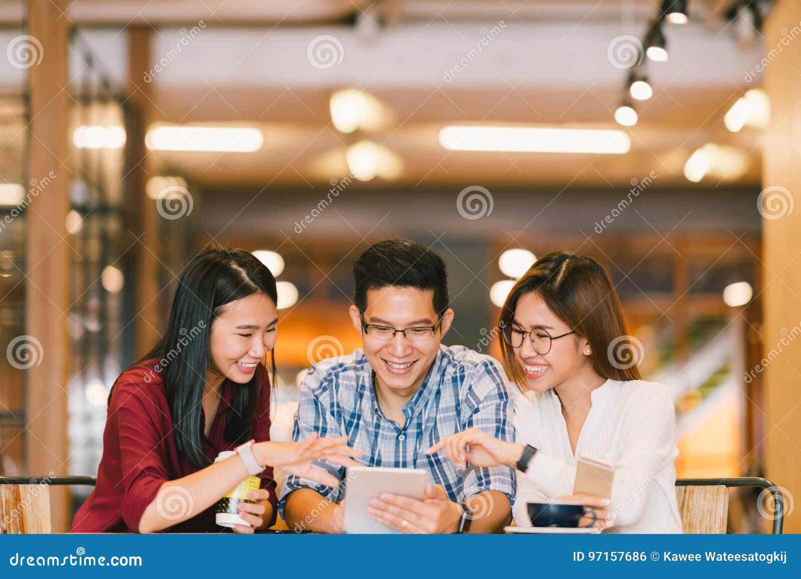 Junge asiatische Studenten oder Mitarbeiter, die zusammen digitale Tablette an der Kaffeestube, verschiedene Gruppe verwenden Zuf