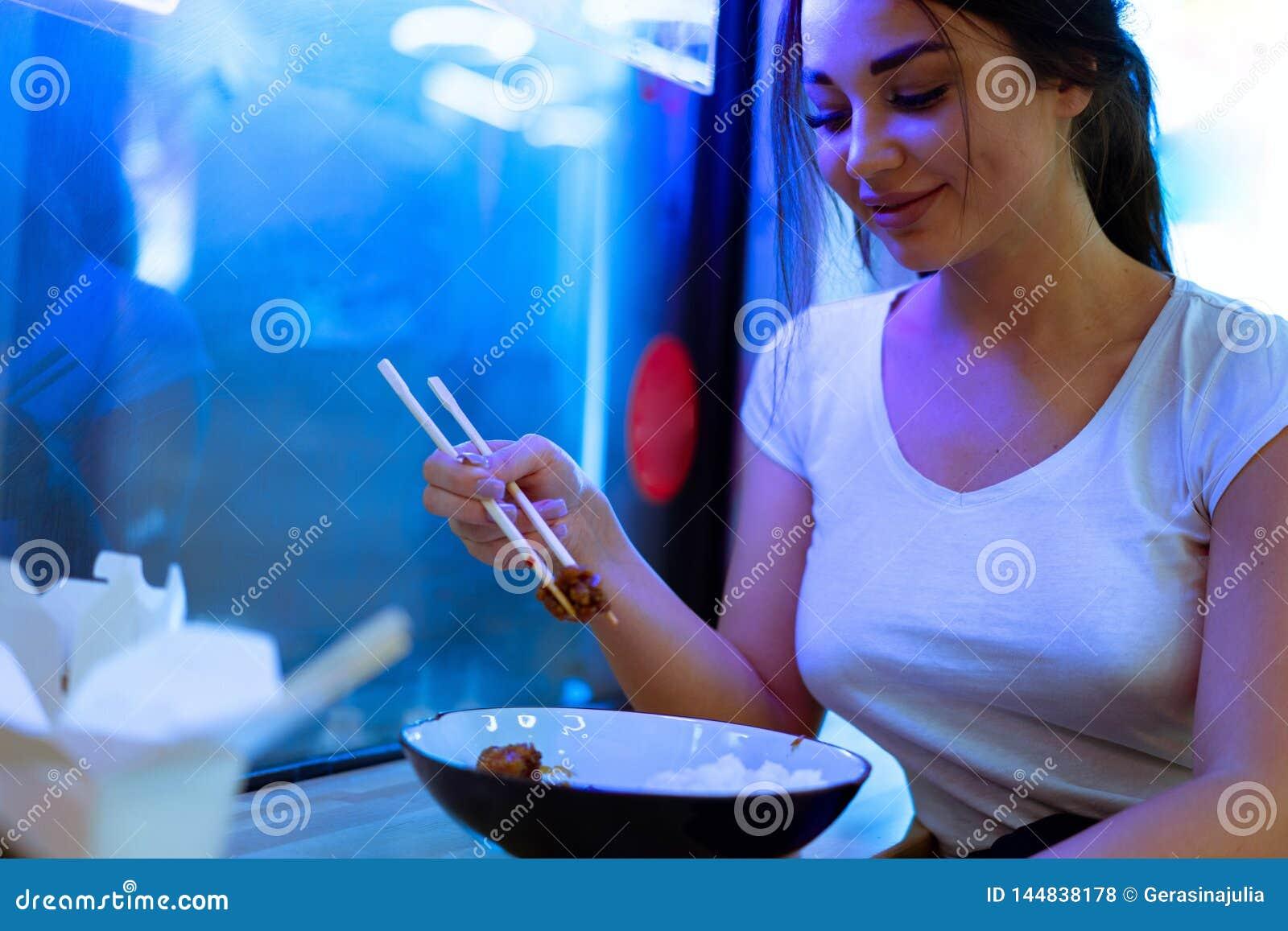 Junge attraktive Frau, die asiatische Nahrung mit Essst?bchen am Caf? oder am Restaurant isst