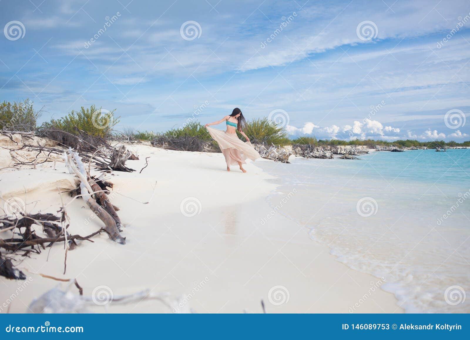 Junge attraktive Frau im Bikini und im langen Rock Schönes Mädchen genießt die Sommersonne
