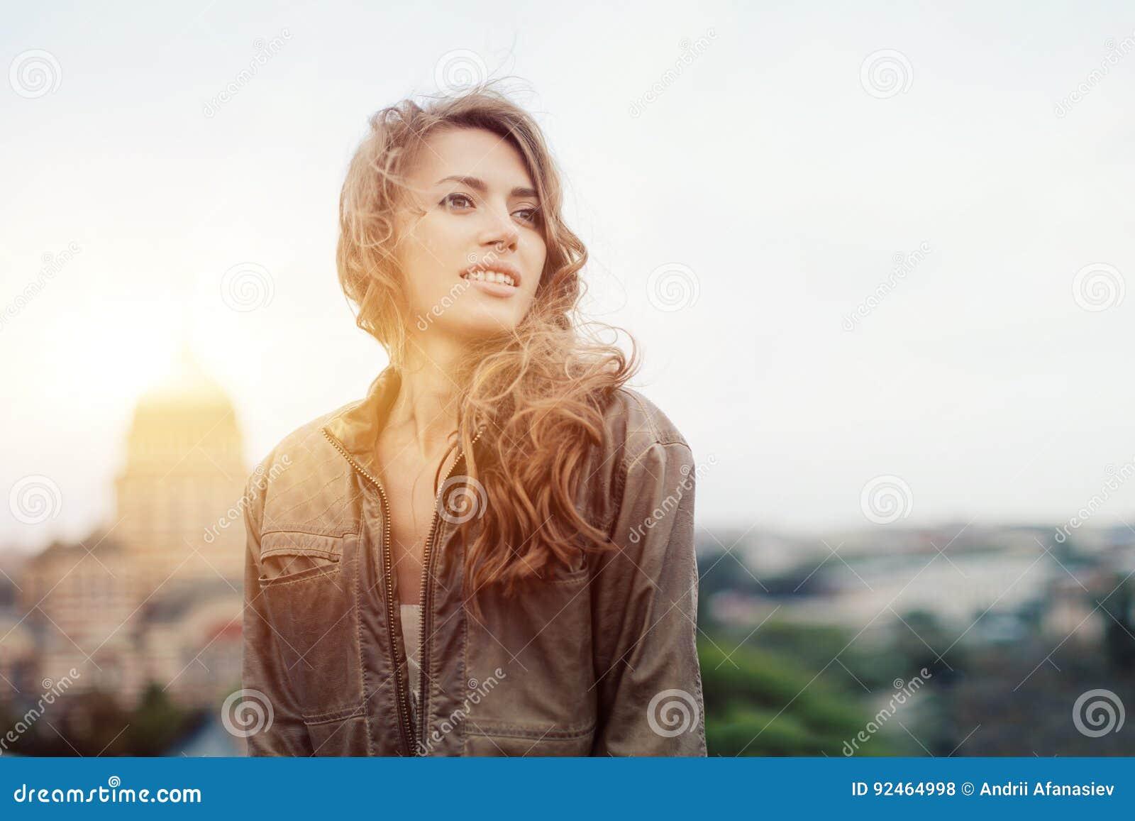 Junge attraktive Frau mit guter Laune schöne Stadtlandschaft bei der Stellung genießend auf einem Dach des Gebäudes, bezaubernde