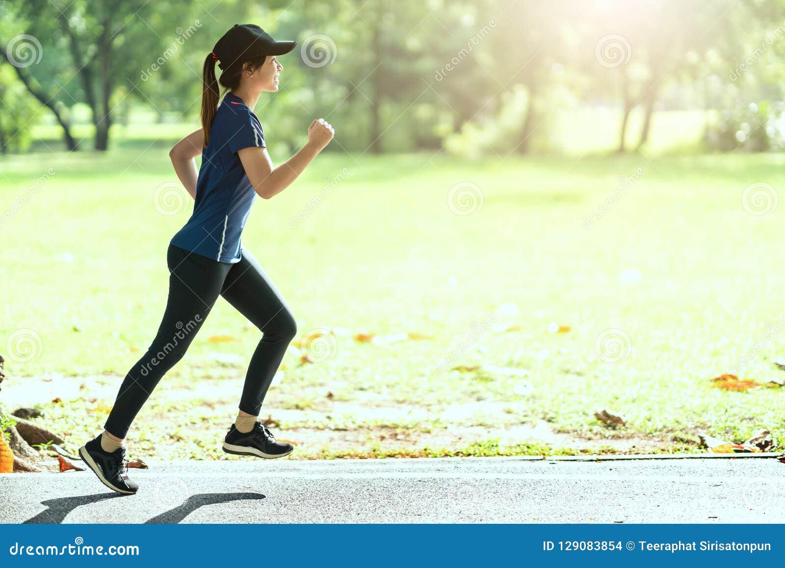 Junge attraktive glückliche asiatische Läuferfrau, die öffentlich den Naturstadtpark trägt sportliche Sportkleidung mit Kopienrau