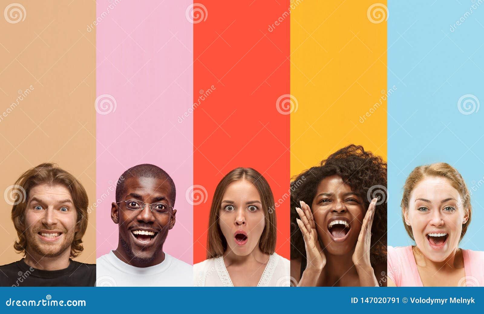 Junge attraktive Leute, die auf mehrfarbigem Hintergrund erstaunt schauen