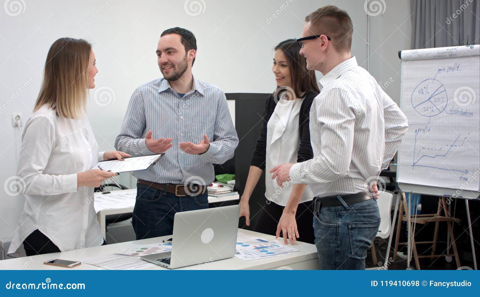 Junge Büroangestellte, die Spaß während des Geschäftstreffens haben