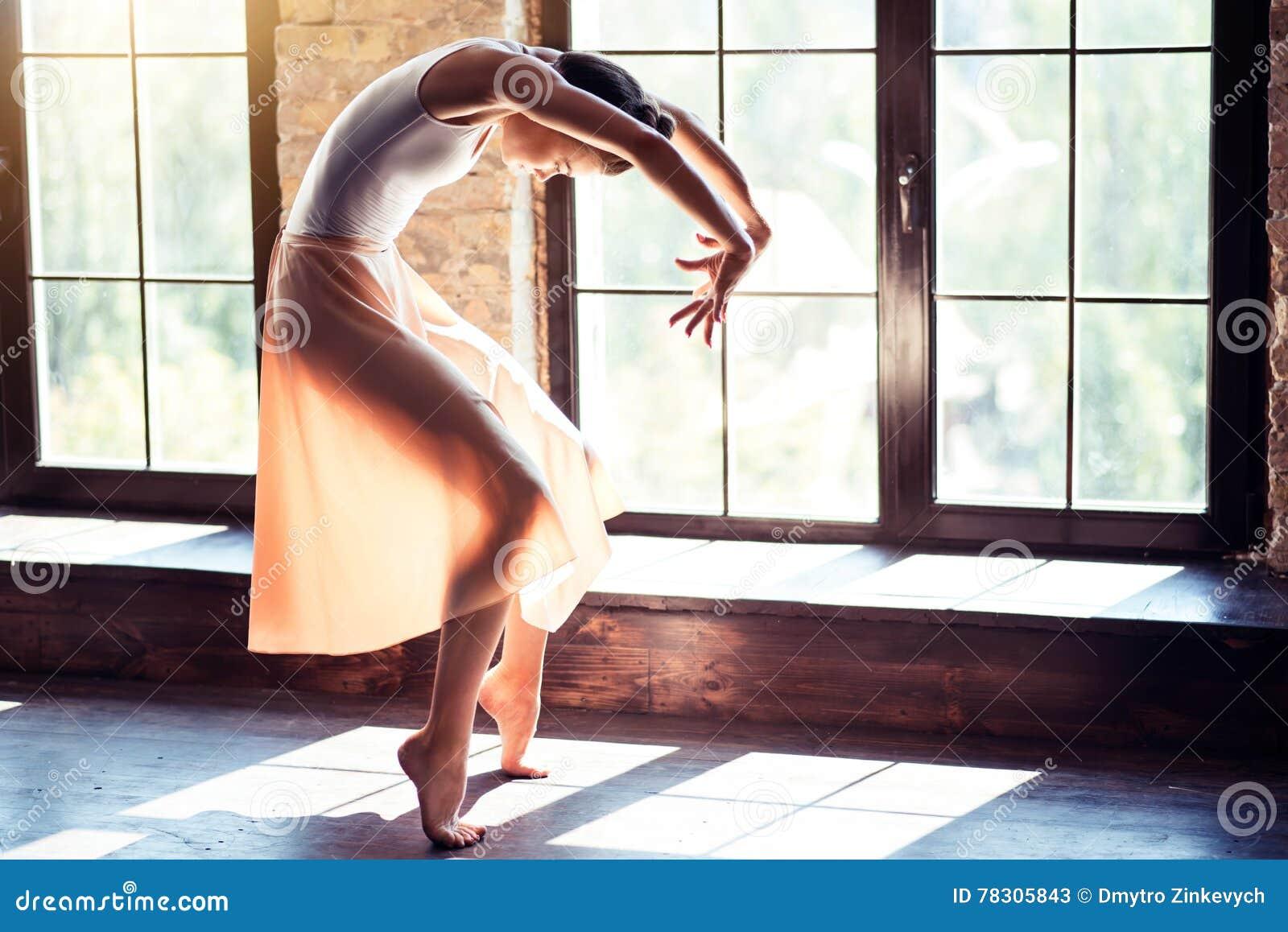 Junge Ballerina, die ihren Tanz in einer Turnhalle probt