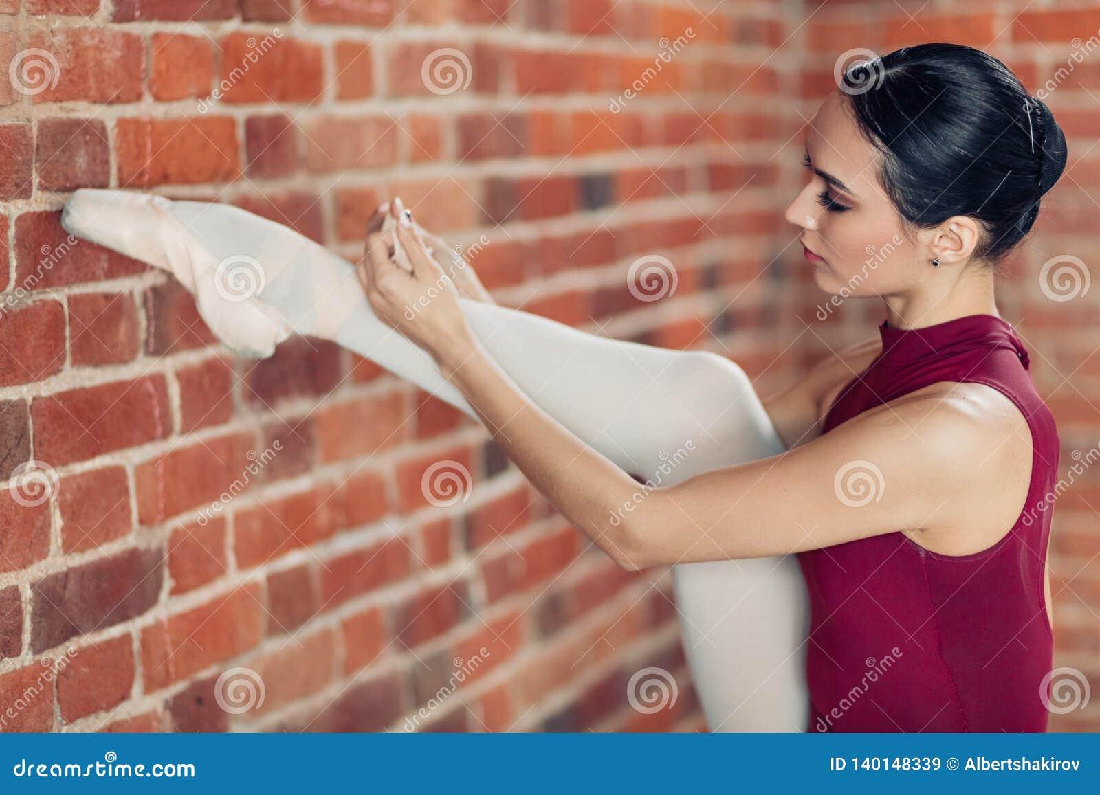 Junge Ballerina mit dem angehobenen Bein, welches das Band in ihren Schuhen bindet