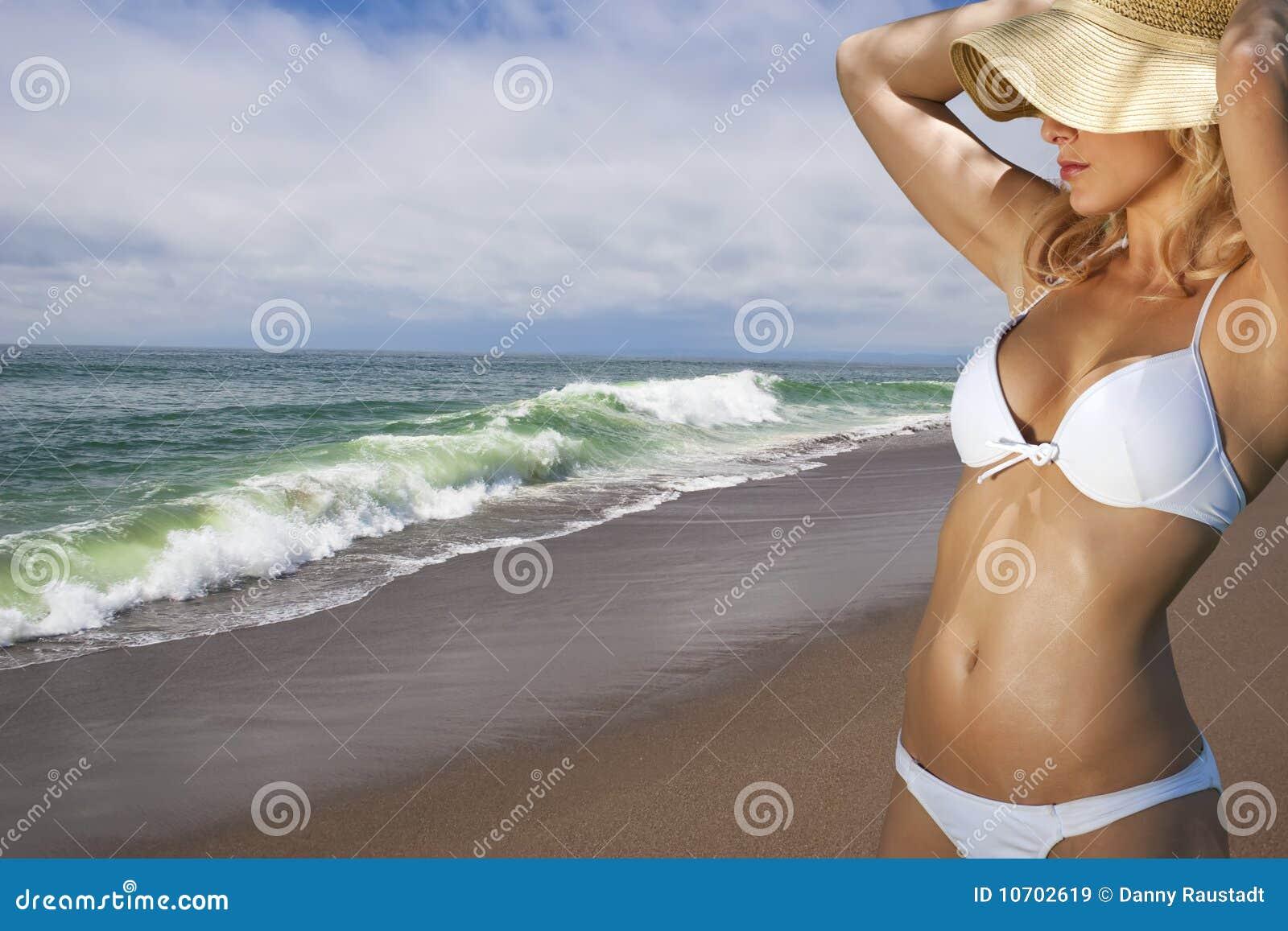 Junge blonde Frau, die am Strand vacationing ist