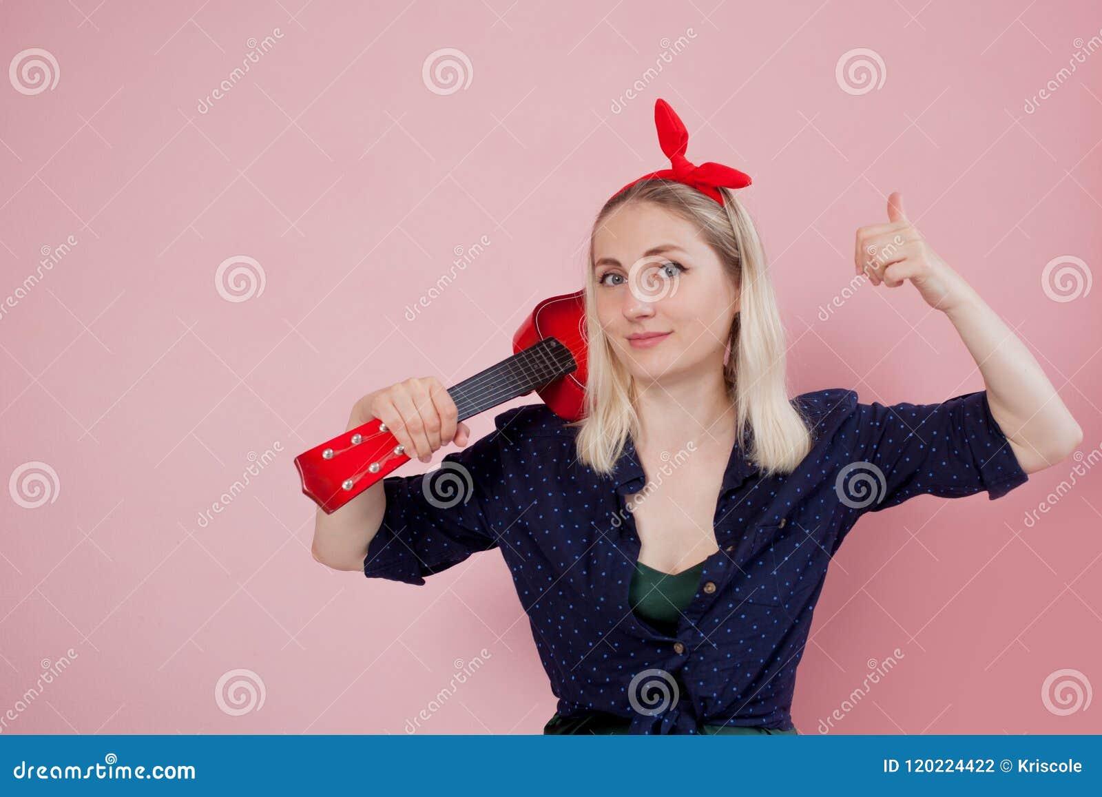 Junge blonde Frau mit einer Ukulele auf Schulter Zeigt sich eine Fingergeste Es ` s groß