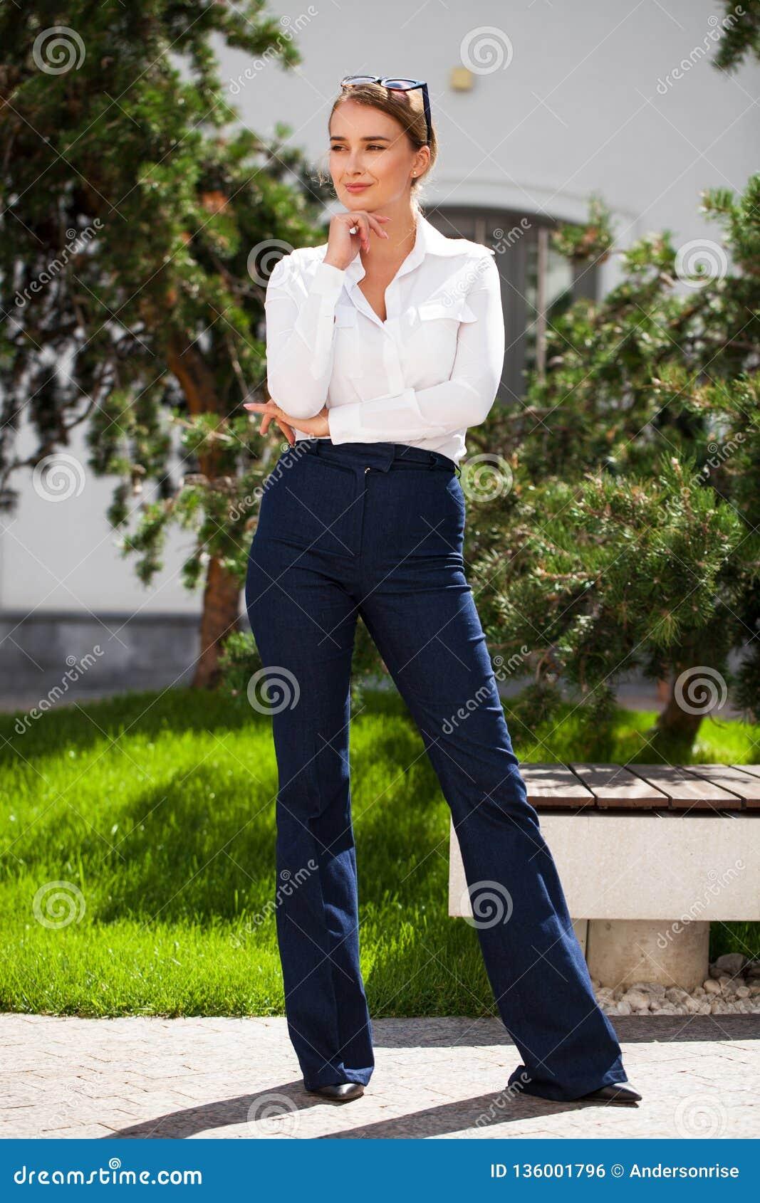 Junge blonde Geschäftsfrau in den Blue Jeans und im weißen Hemd