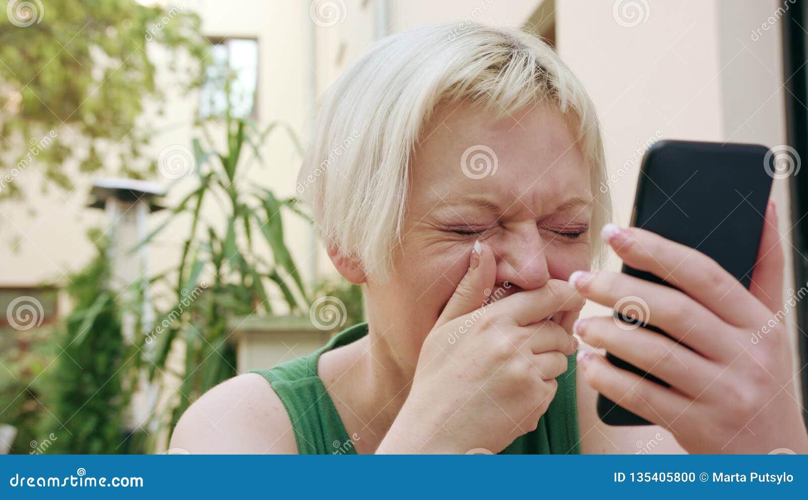 Junge Blondine, die außerhalb und unter Verwendung des Telefons sitzen