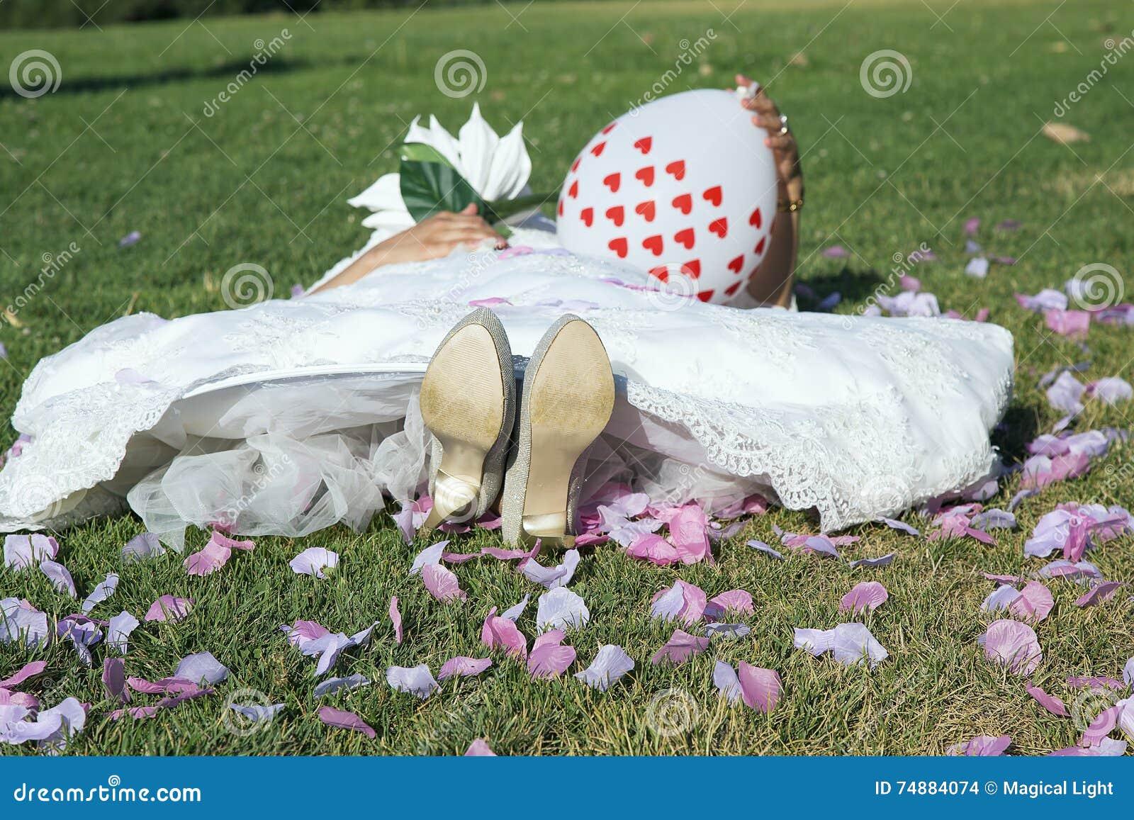 Junge Braut, die auf dem Gras liegt