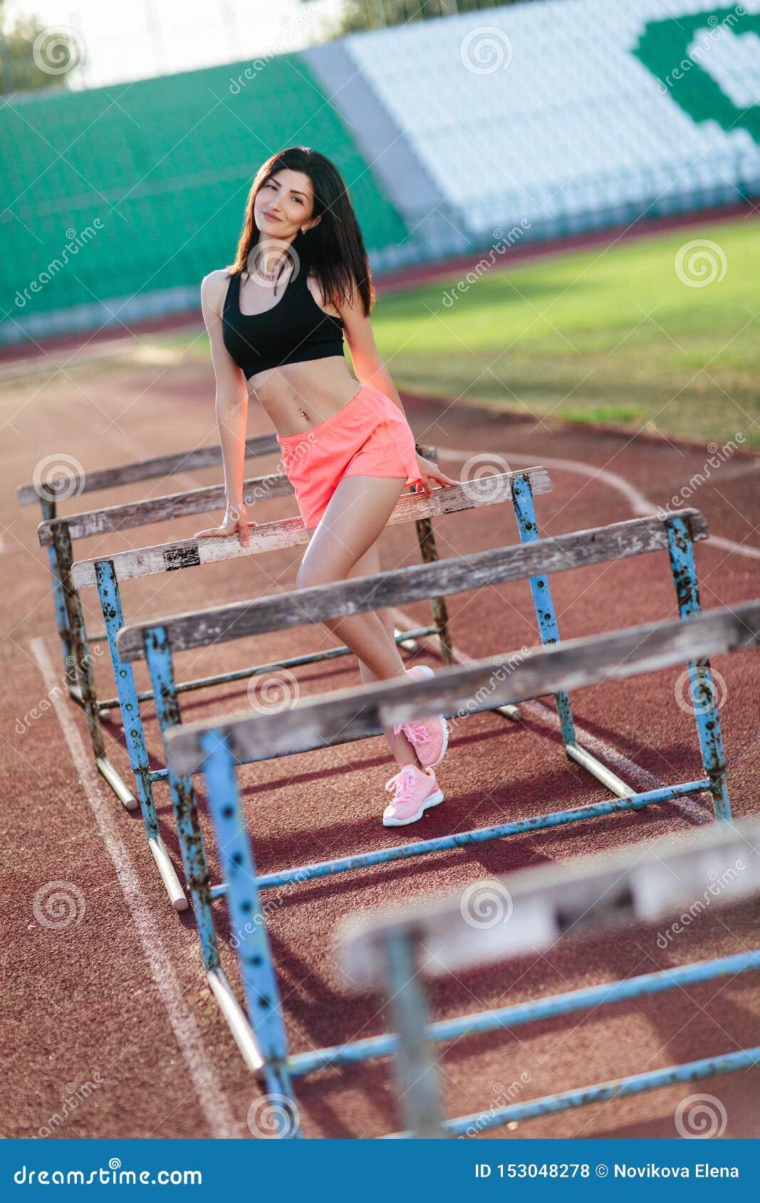 Junge brunette Sportlerin auf sportlicher Lebensstilstellung des Stadions auf der Bahn, die nahe den Sperren laufen lassen das Sp