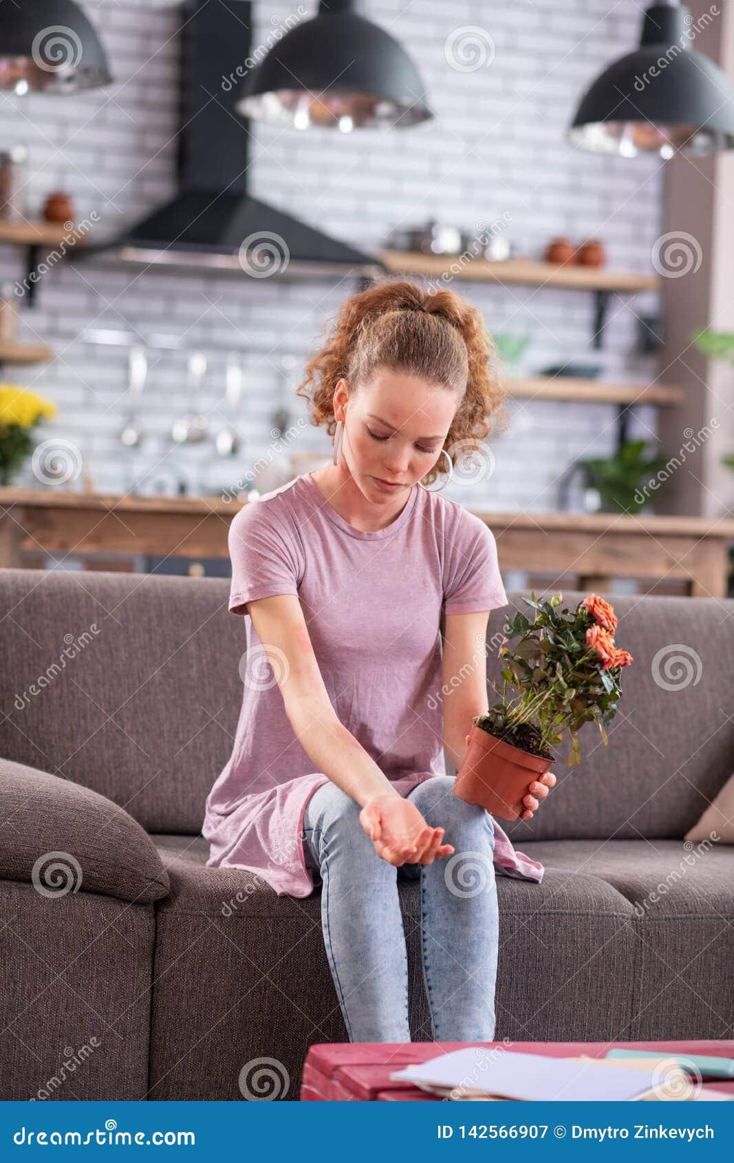 Junge Dame des elenden Ingwers, die auf grauer Couch mit Topf sitzt