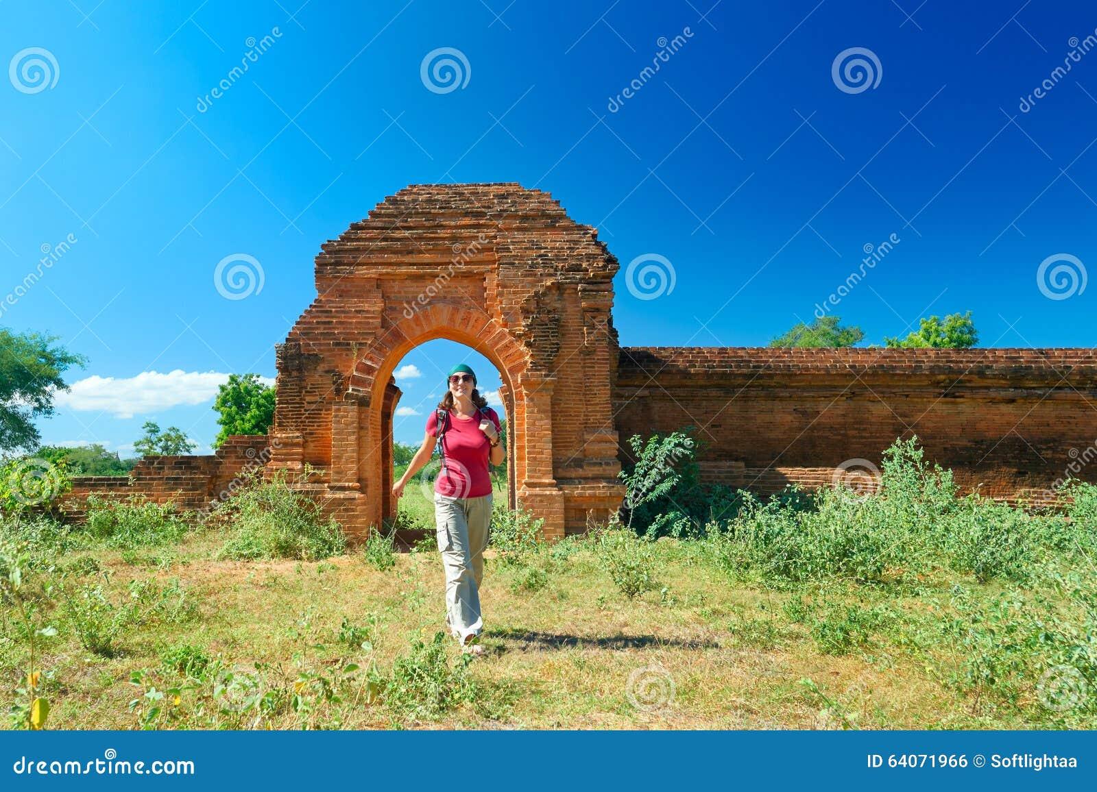 Junge Dame mit einem Rucksack aus den Toren der alten Ruinen heraus