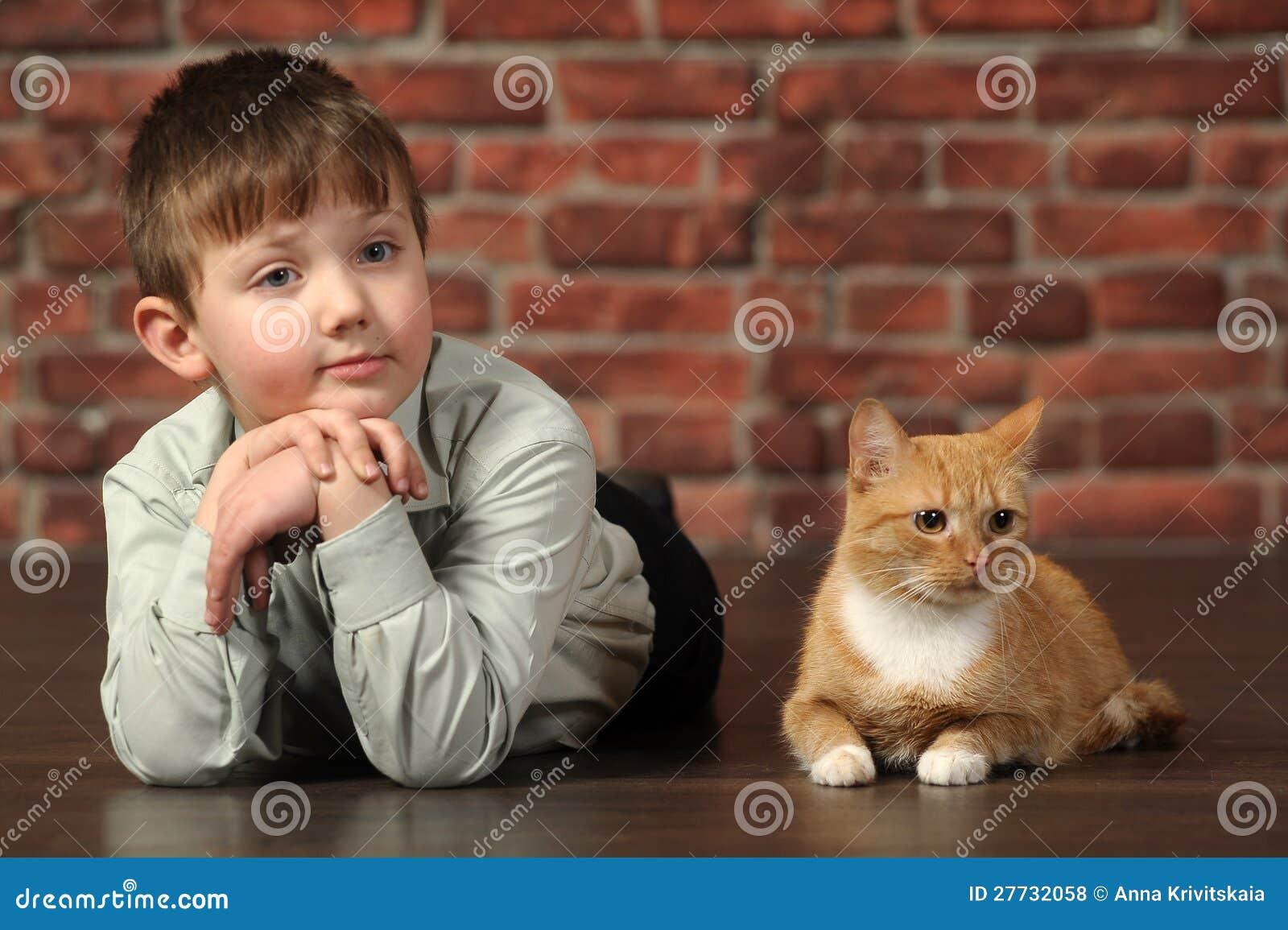 Junge, der auf dem Boden mit Katze liegt