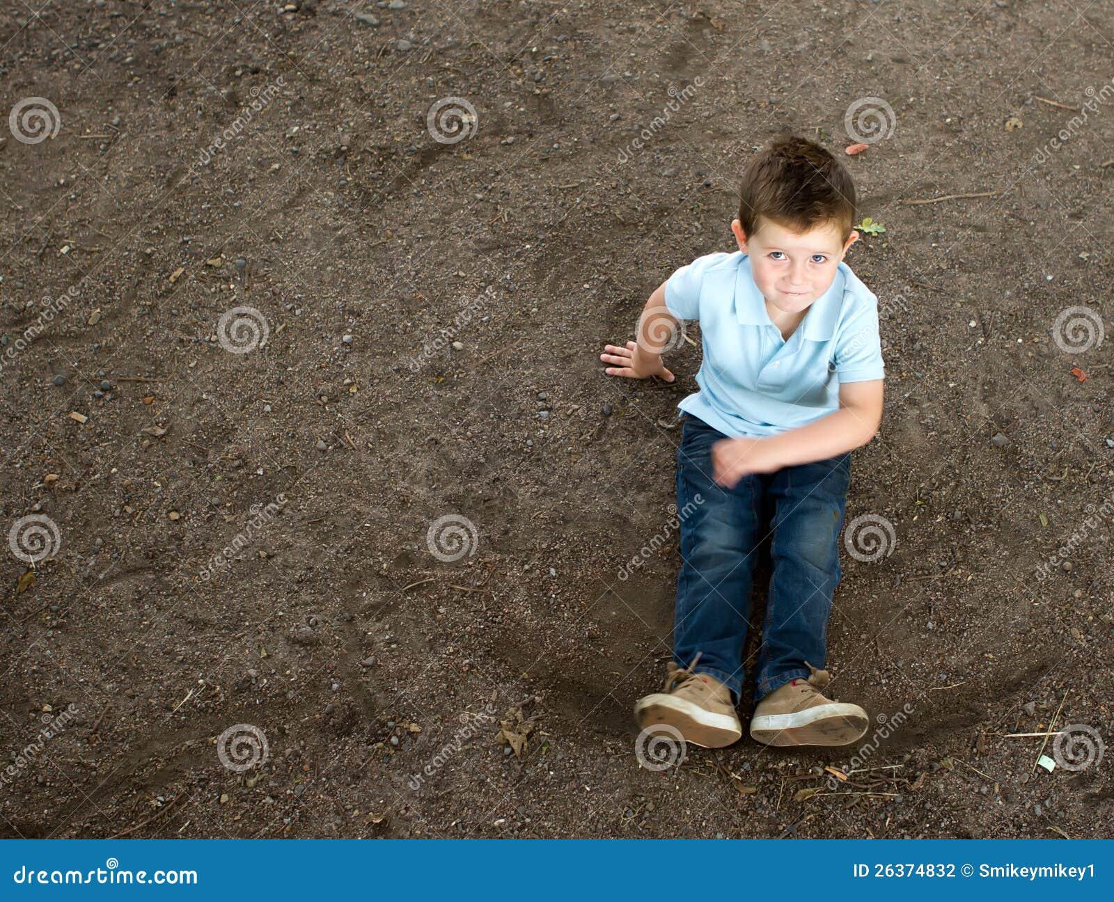 Junge, der auf einem steinigen Waldpfad sitzt