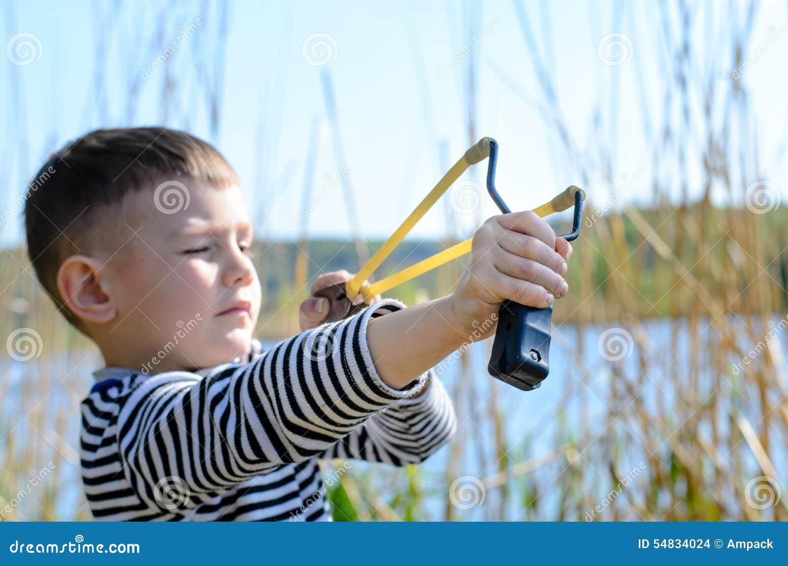 Junge, der draußen Riemen-Schuss durch See zielt