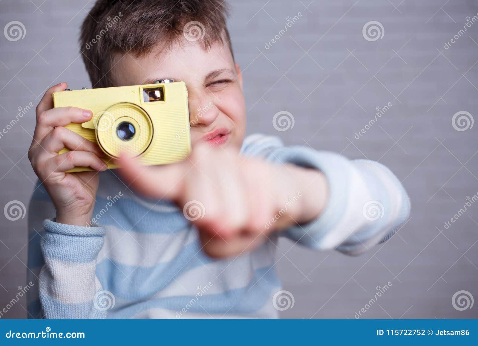 Junge, der ein Foto mit der Weinlesekamera zeigt auf Sie macht Photog
