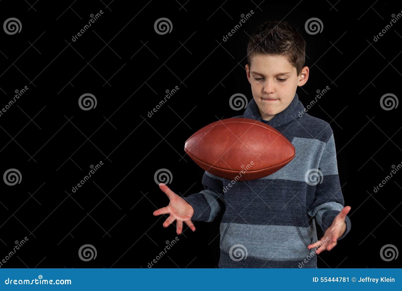 Junge, der herauf Fooball und das Fangen wirft