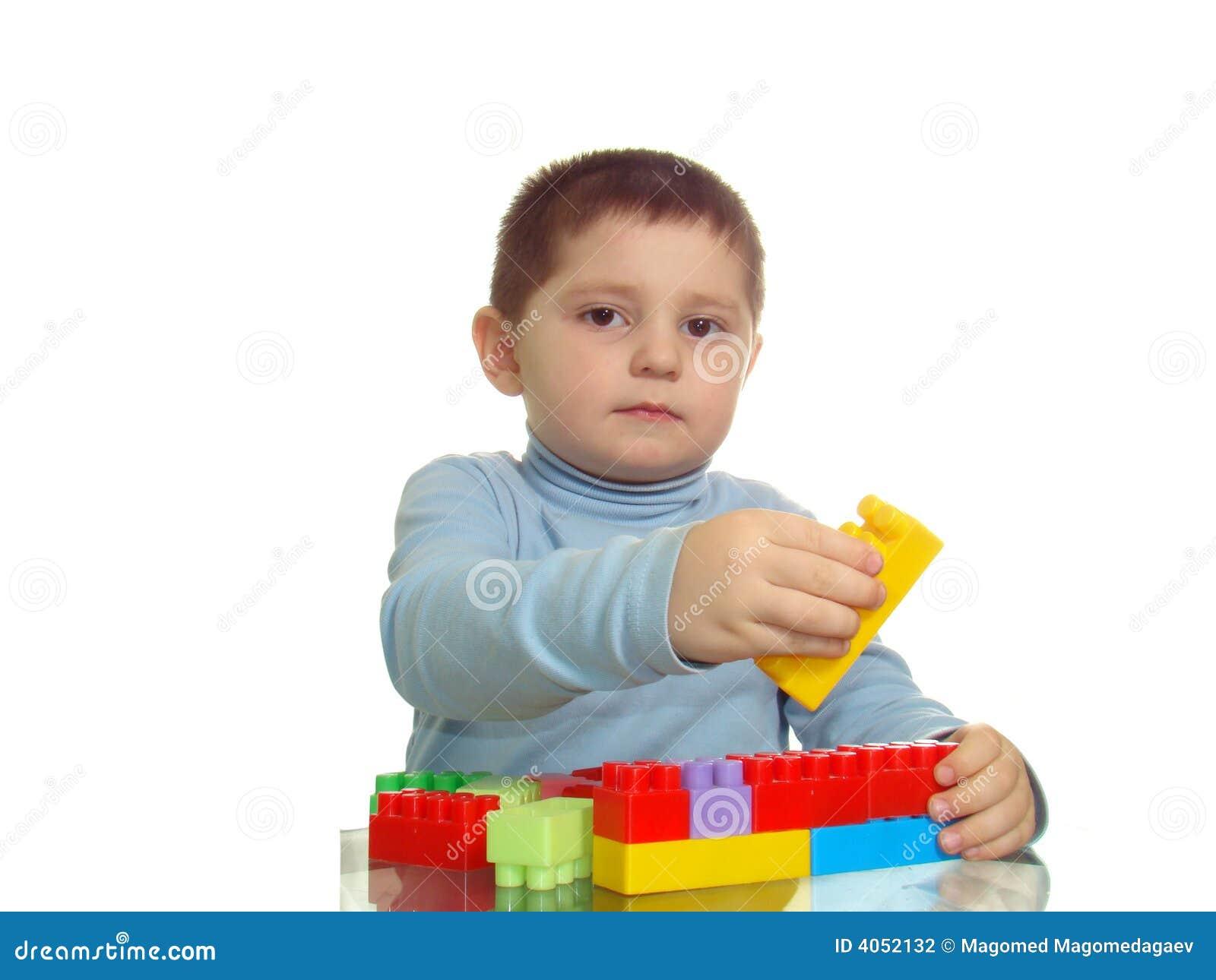 Junge, der mit den Ziegelsteinen schauen zur Kamera spielt