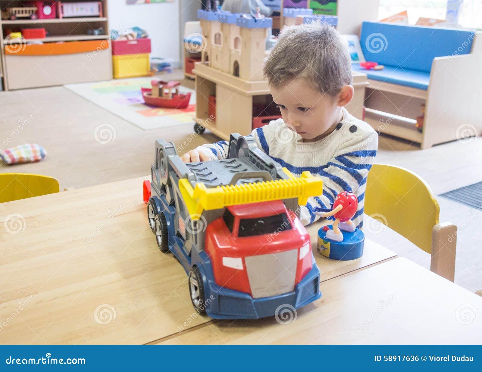 Junge, der mit Spielwaren im Kindergarten spielt