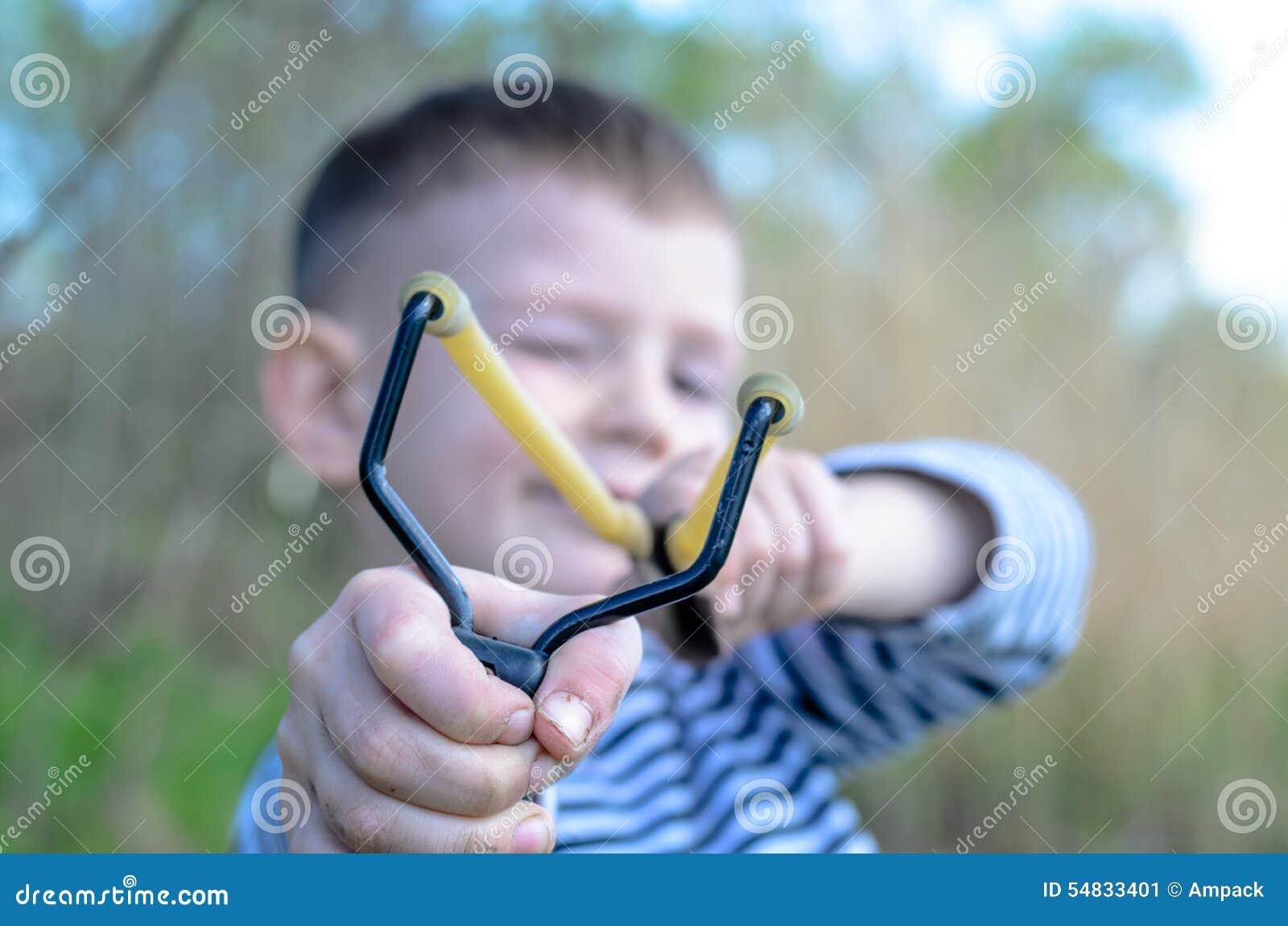 Junge, der Riemen-Schuss auf Kamera abzielt