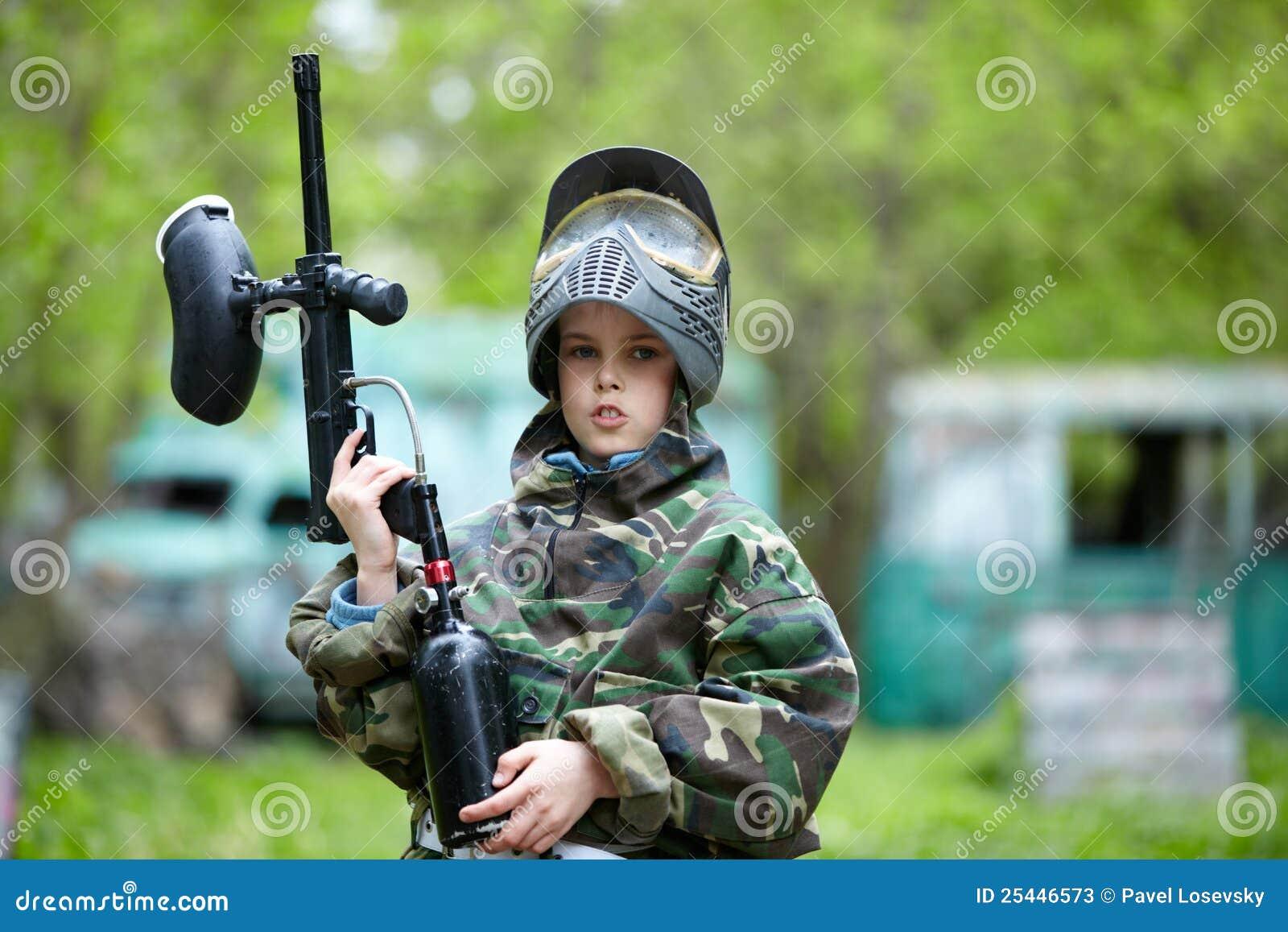 Junge in der Tarnung hält ein Paintballgewehrfaß hoch