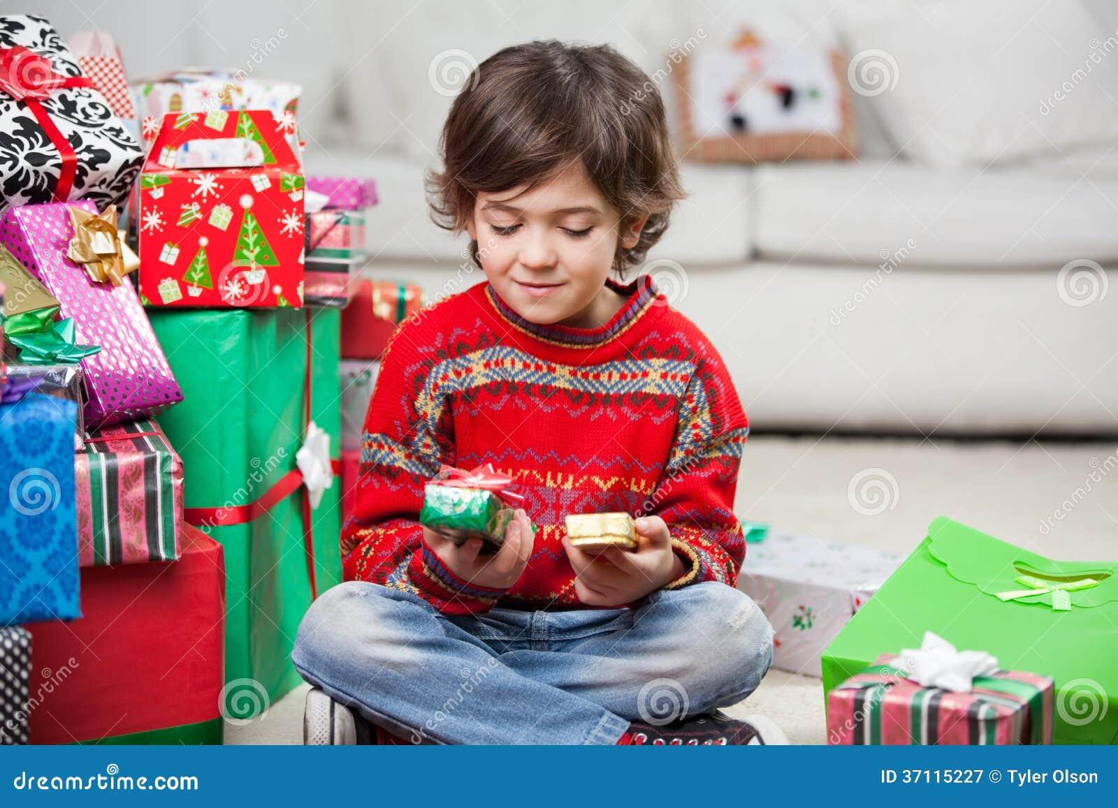 Junge, Der Weihnachtsgeschenke Betrachtet Stockbild - Bild von ...