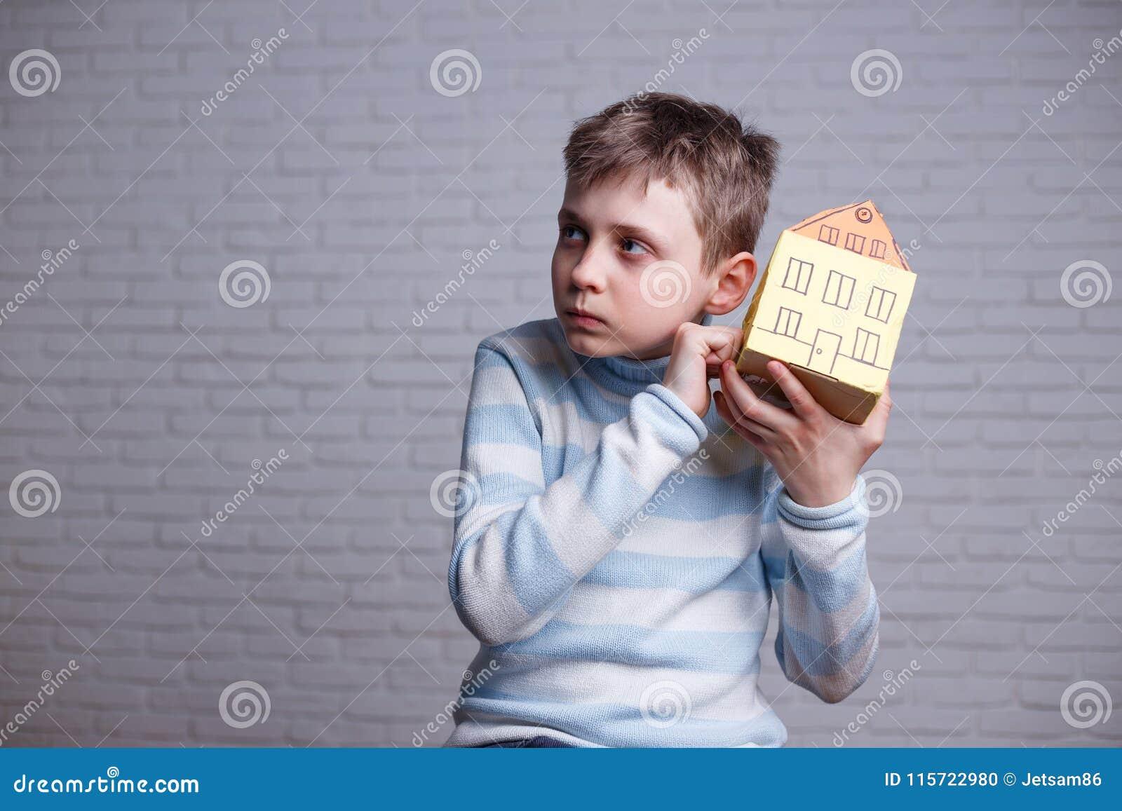 Junge, der zum Pappspielzeughaus und -c$hören klopft Jugendlich und chil