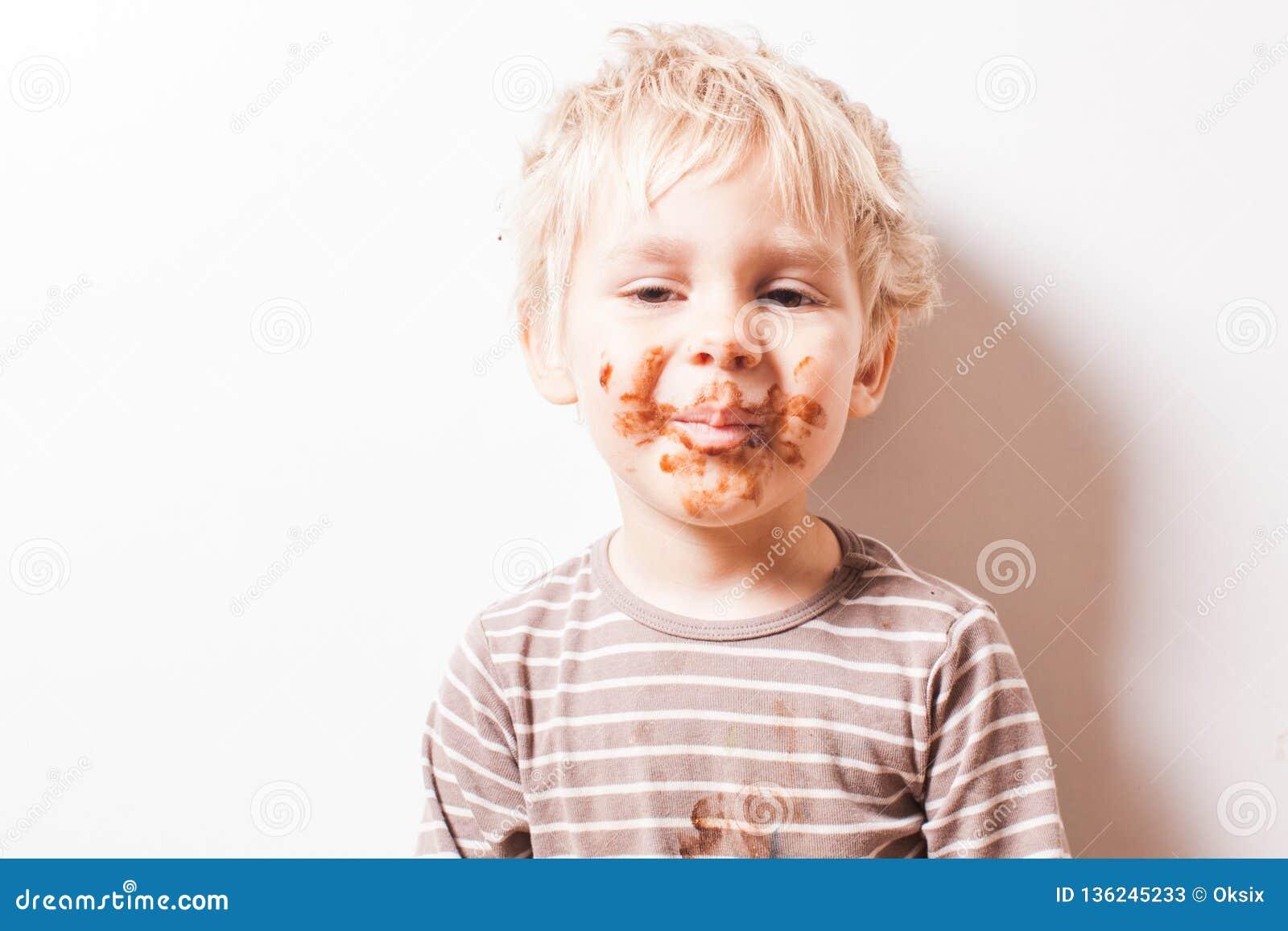 Junge eated Schokolade, lustiges schmutziges gelächeltes Gesicht