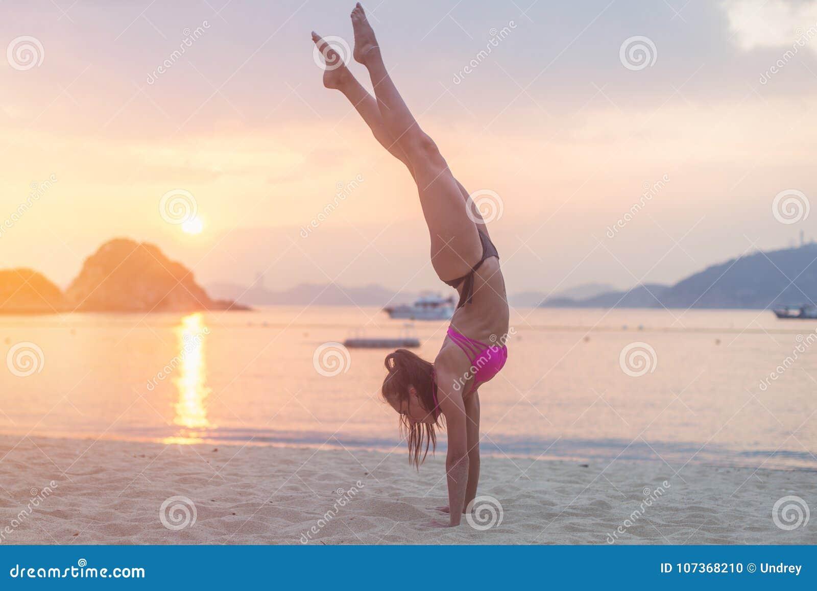 Junge Eignungsfrau, die Handstandübung auf Strand bei Sonnenaufgang tut Sportliches Mädchen in übender Yogaküste des Bikinis
