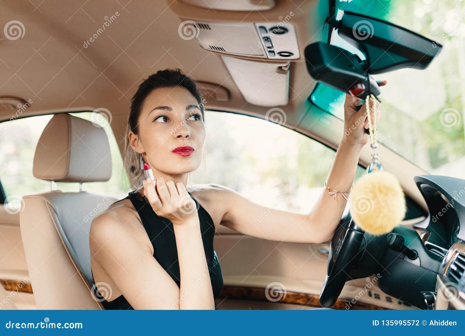 Junge elegante Frau, die im Autoansichtspiegel-Weile applyin schaut
