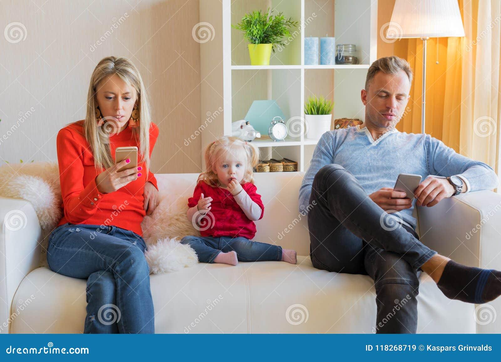Junge Eltern ignorieren ihr Kind und das Betrachten ihrer Handys