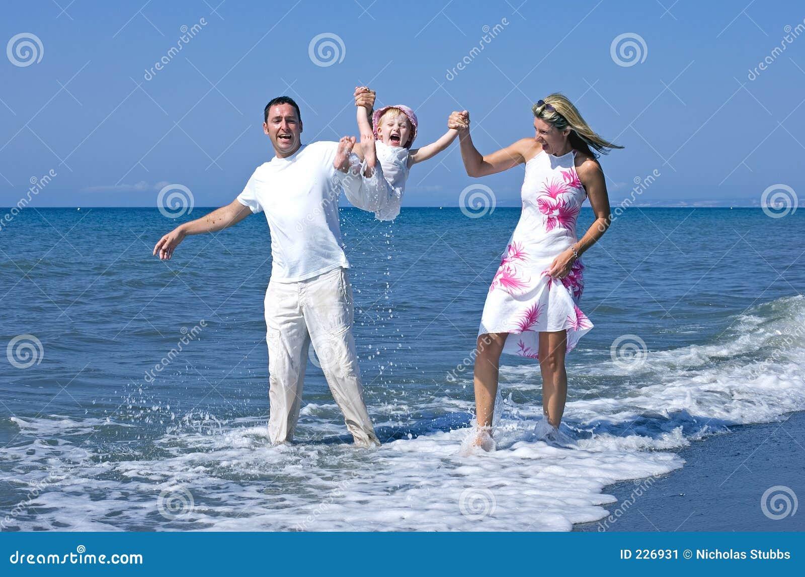 Junge Familie, die mit Tochter auf Strand in Spanien spielt
