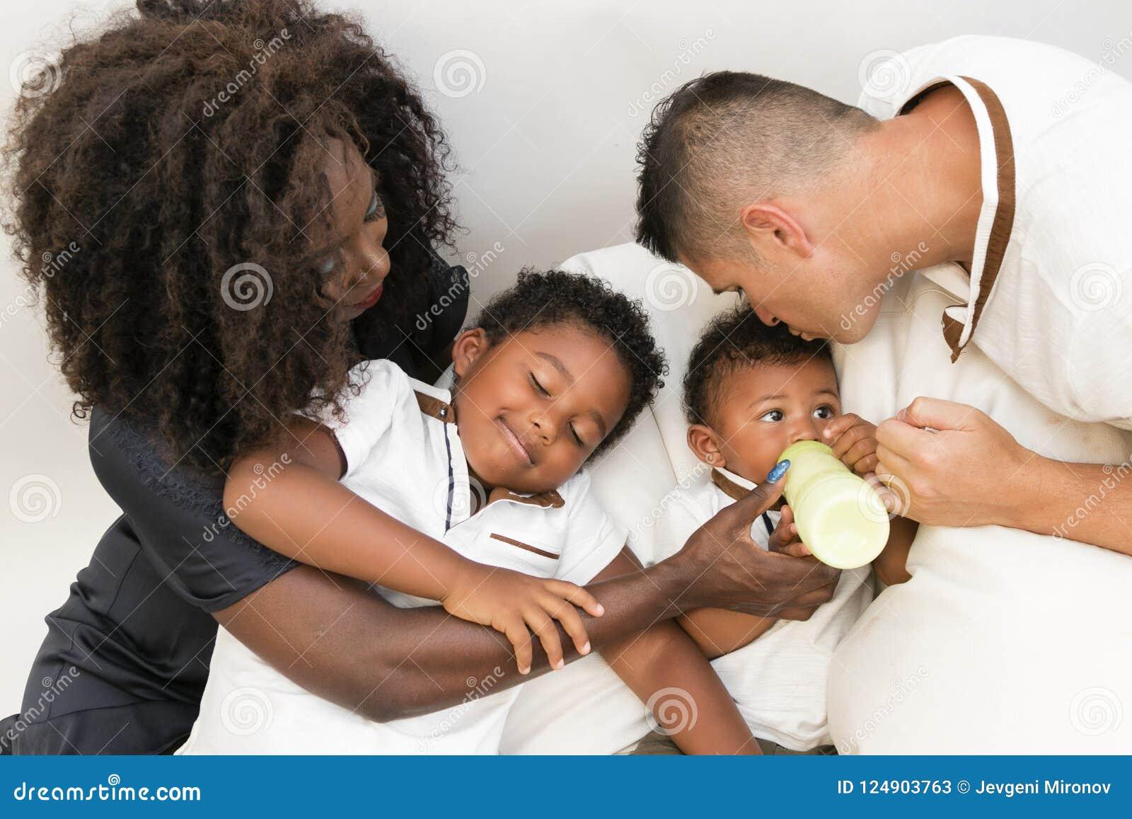 Junge Familie Eltern, die ein Säuglingskind mit Milch einziehen Multi und