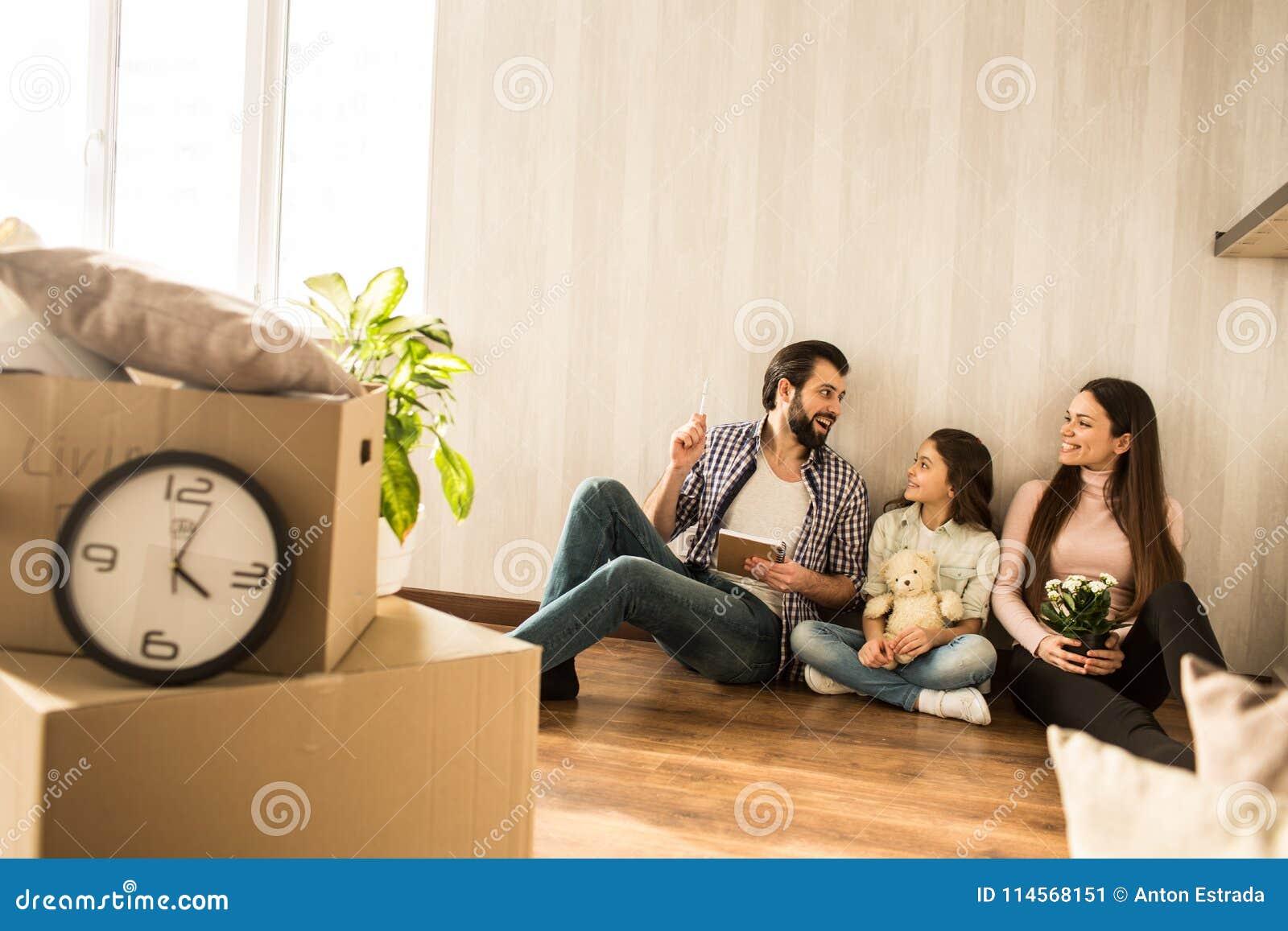 Junge Familie sitzt zusammen auf dem Boden im Wohnzimmer Sie haben in diese Wohnung gerade sich bewegen Mädchen sind