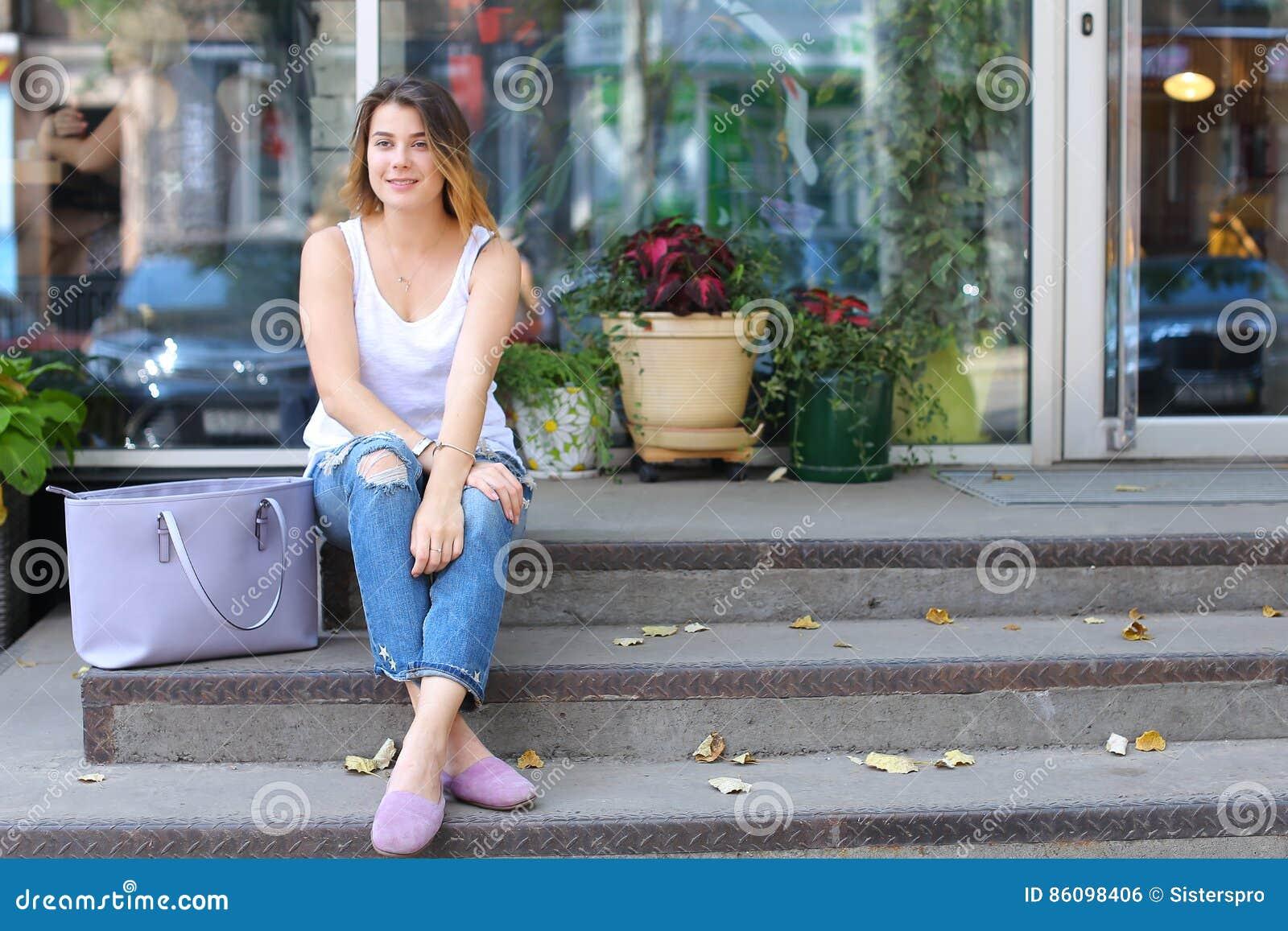 Junge Frau auf dem Boden auf der Straße, die in camera unter Verwendung p schaut