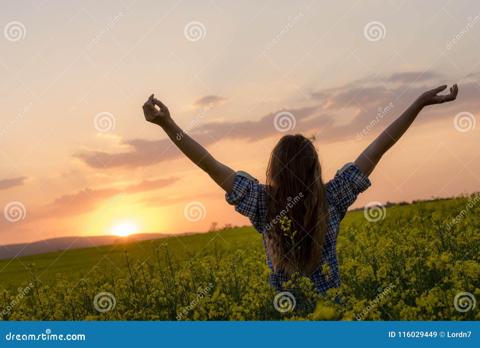 Junge Frau auf einem Gebiet des Ölrapssamens in der Blüte im Sonnenuntergang Freiheits- und Ökologiekonzept