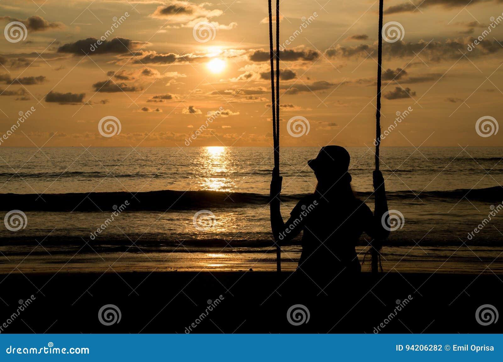 Junge Frau auf einem Schwingen bei Sonnenuntergang