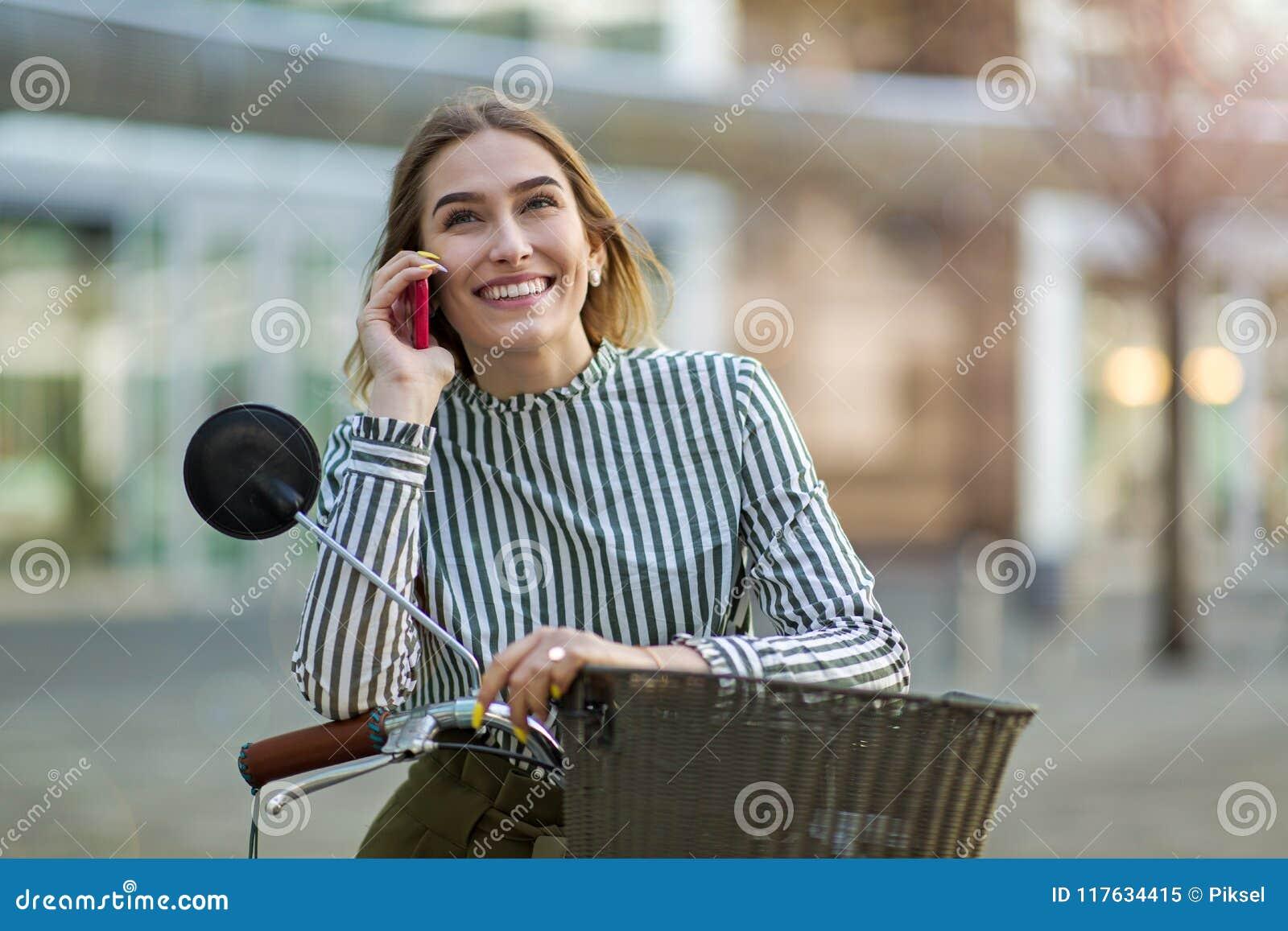 Junge Frau auf Fahrrad unter Verwendung des Handys