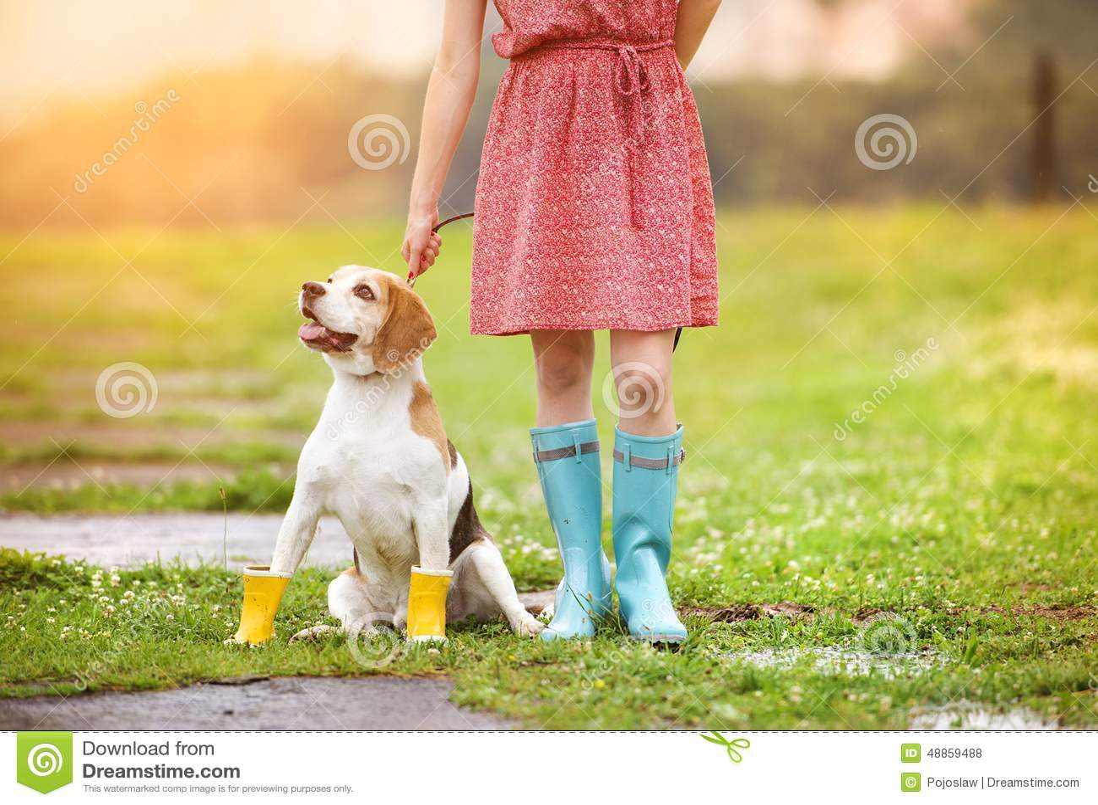 Junge Frau in den Gummistiefeln gehen ihr Hund