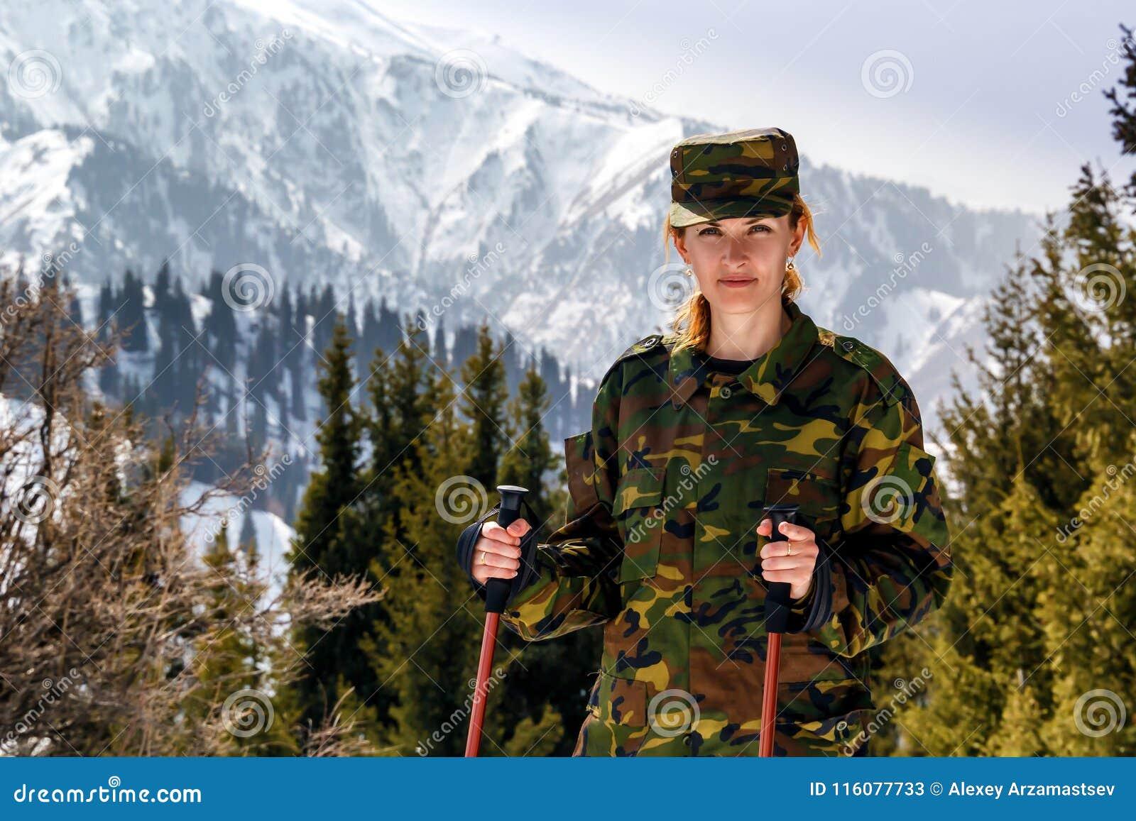 Junge Frau in der kakifarbigen Uniform mit Spazierstöcken auf einem Hintergrund von Schnee-mit einer Kappe bedeckten Bergen