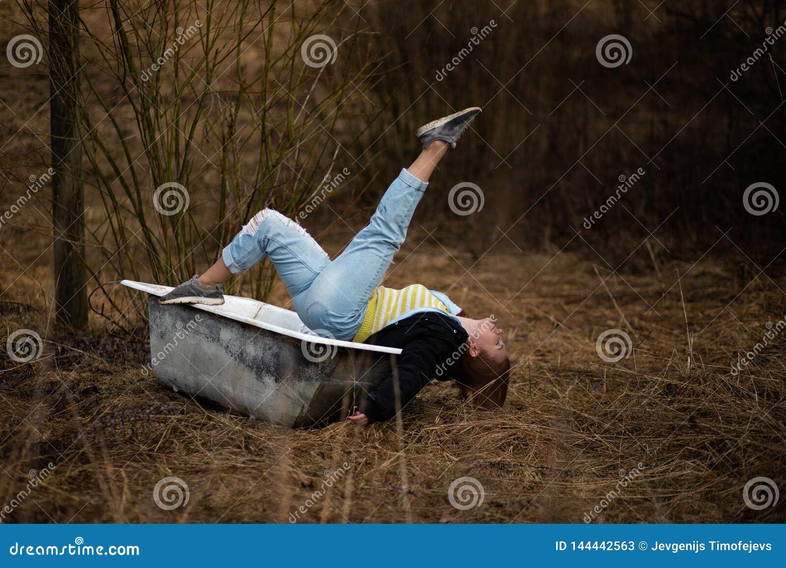 Junge Frau in der Kleidung nimmt ein leeres altes Bad mitten in einem Wald
