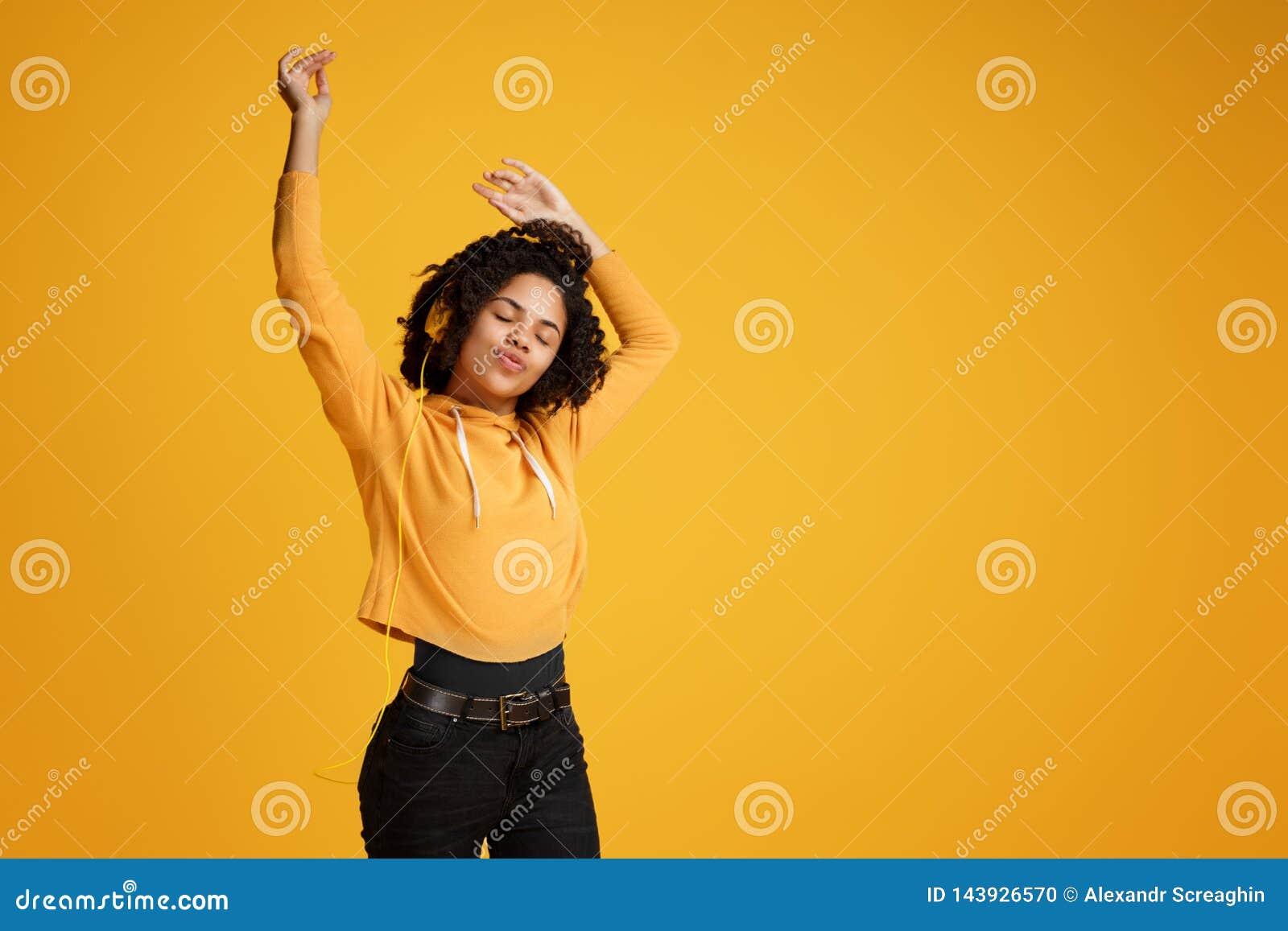 Junge Frau des modischen Afroamerikaners mit hellem L?cheln gekleidet in h?render Musik der Kleidungs der zuf?lligen Kleidung und