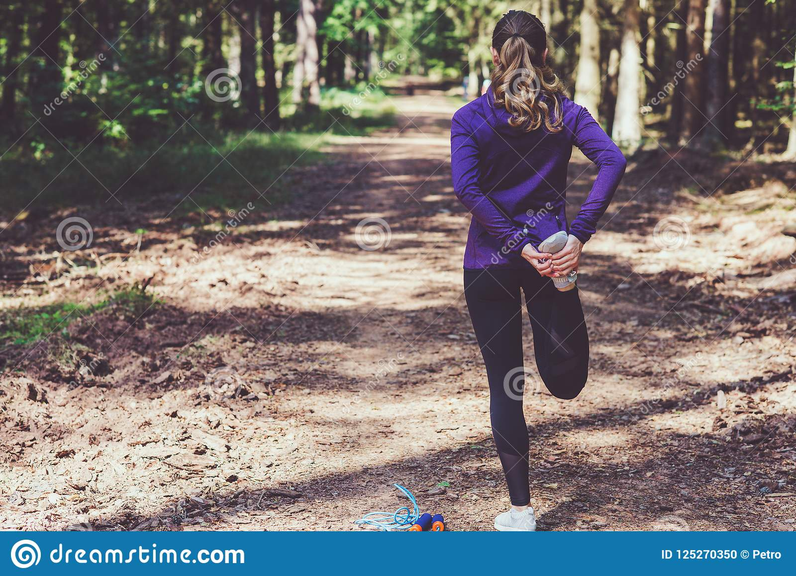 Junge Frau, die Übungen im sonnigen Wald rüttelt und macht