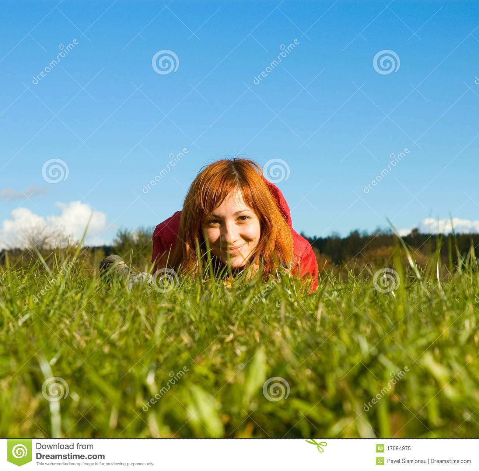 Junge Frau, die auf dem Gras liegt