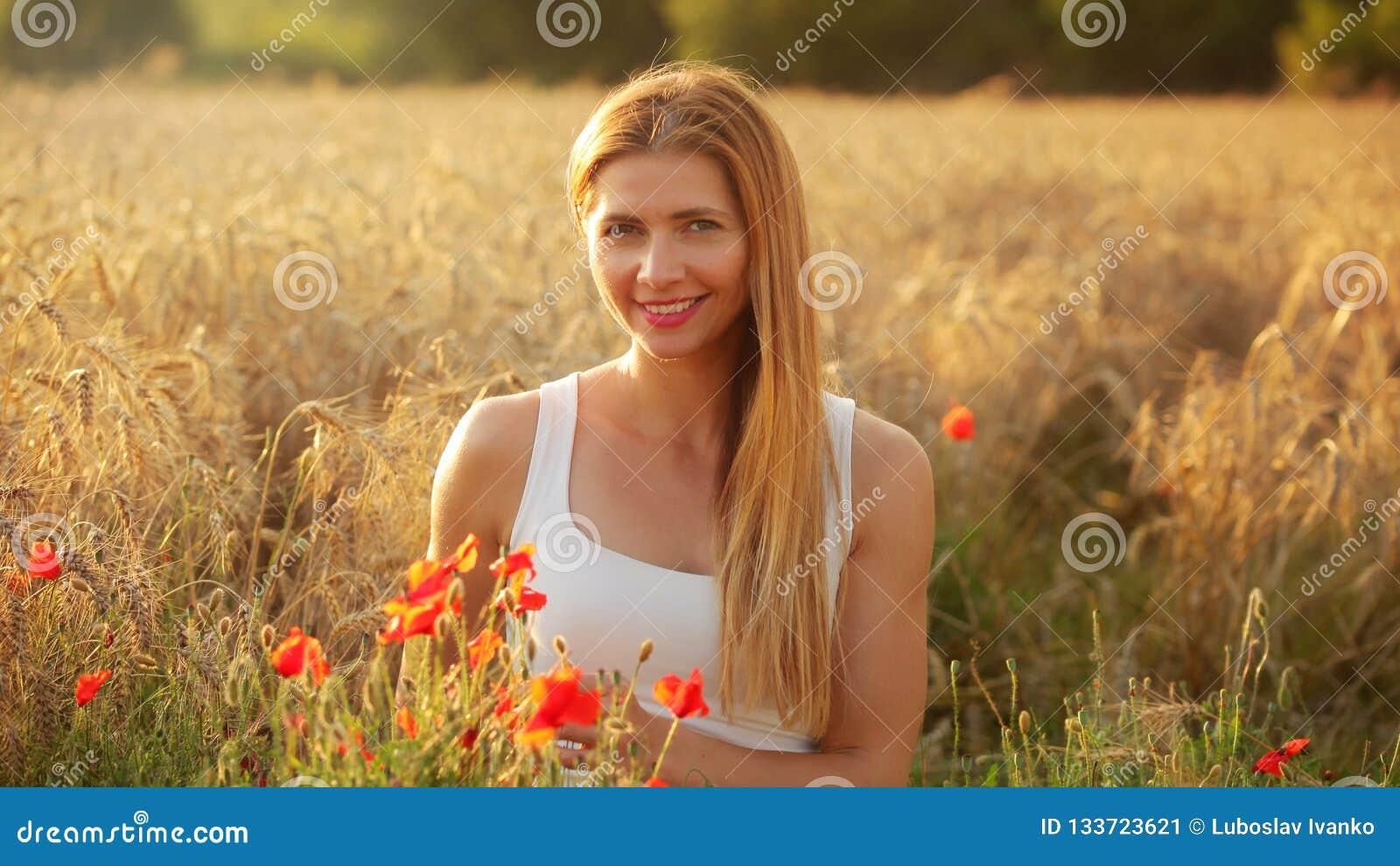Junge Frau, die auf dem Weizengebiet, beleuchtet durch Nachmittagssonne, wenige Re sitzt