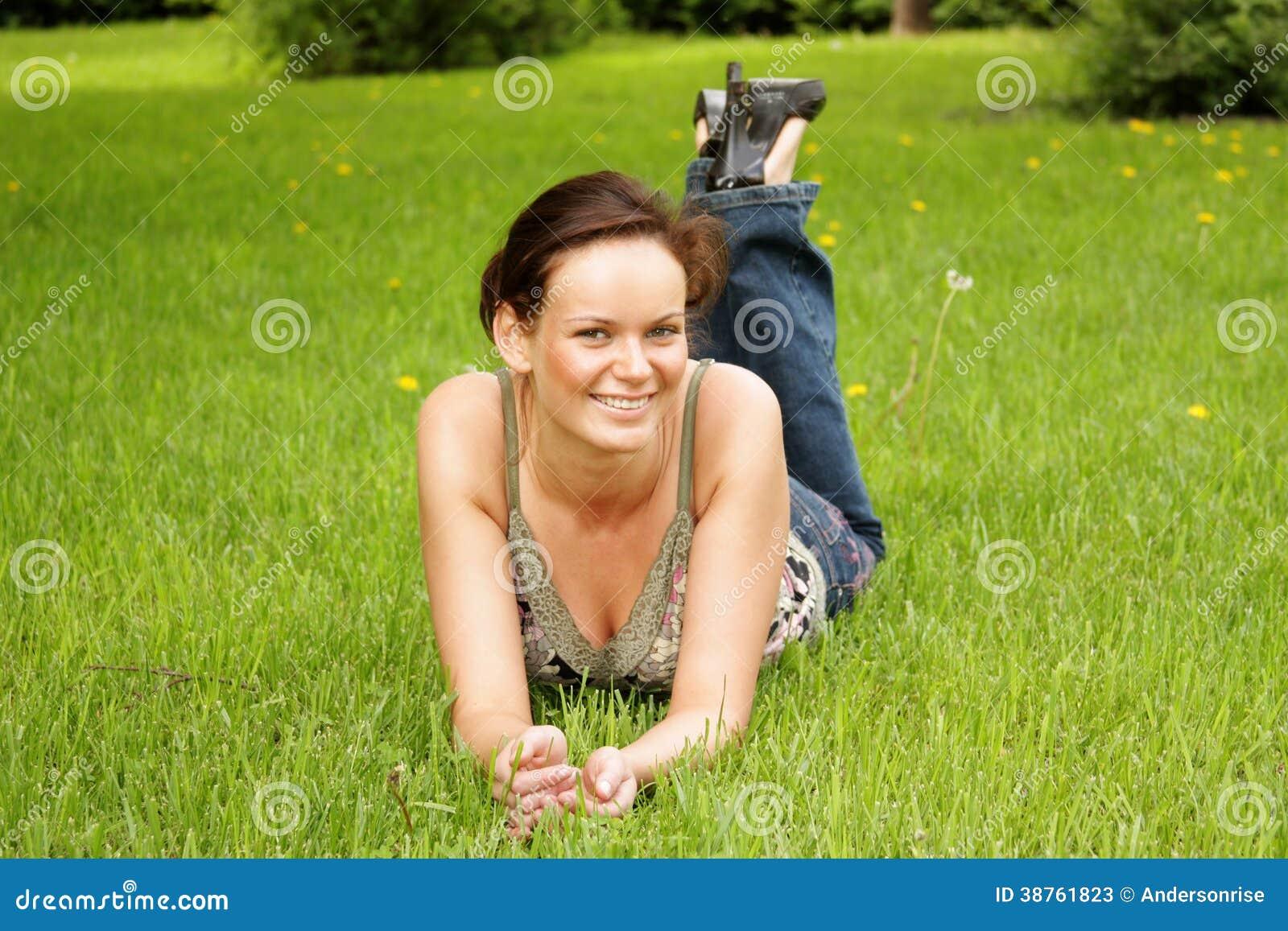 Junge Frau, die auf einem grünen Rasen liegt