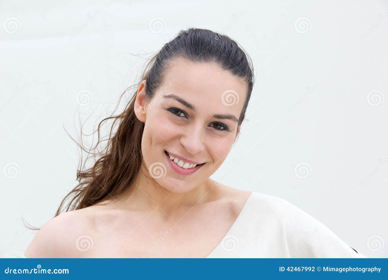 Junge Frau, die auf weißem Hintergrund lächelt