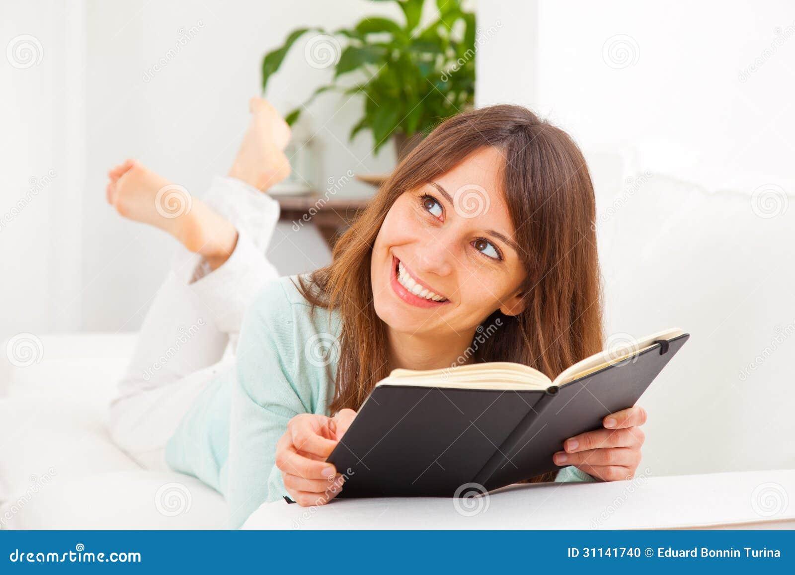 Junge Frau, die bequem auf Couch ausdehnt und ein Buch liest