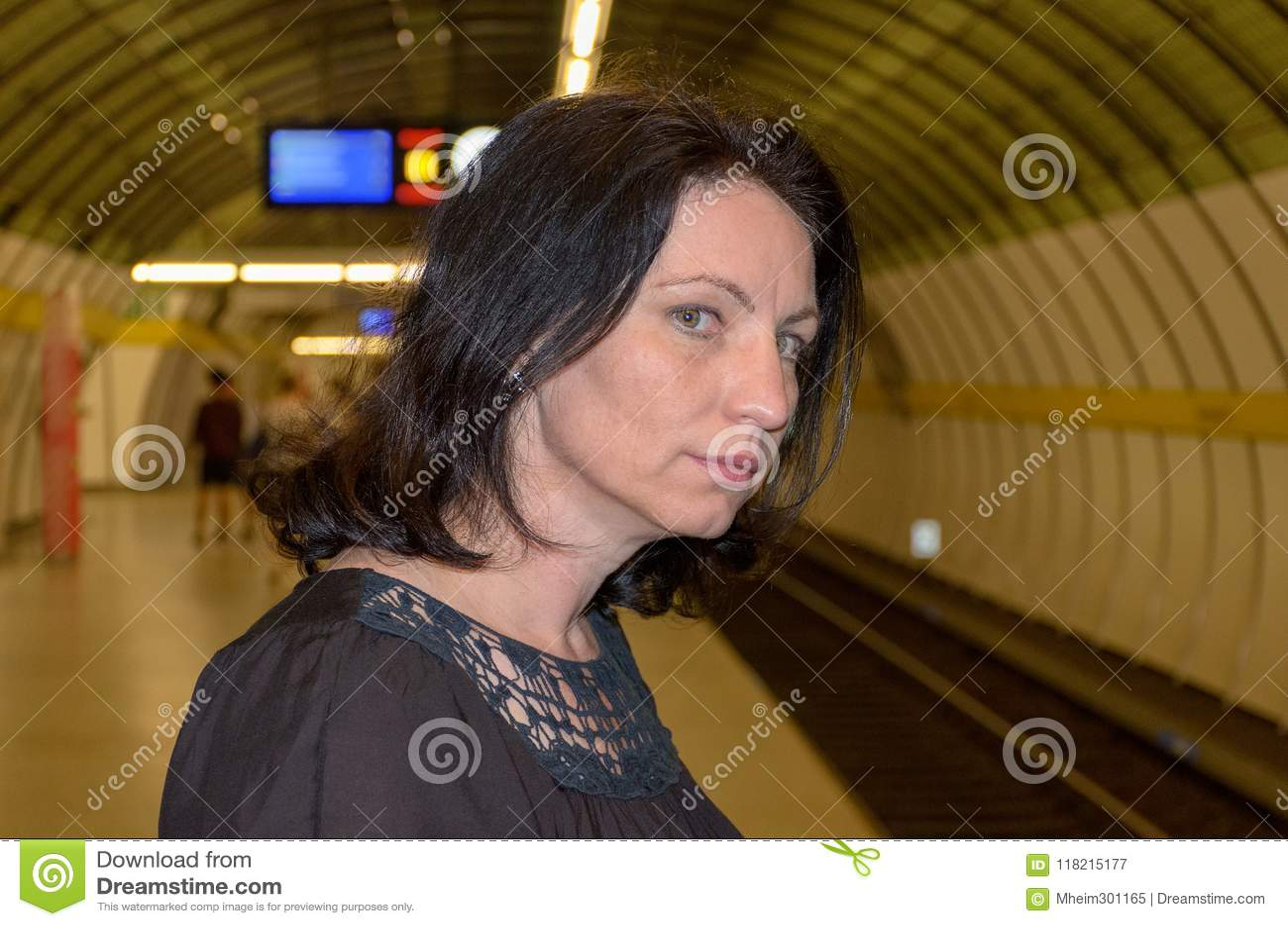 Junge Frau, die besorgt hinunter die Bahnen anstarrt